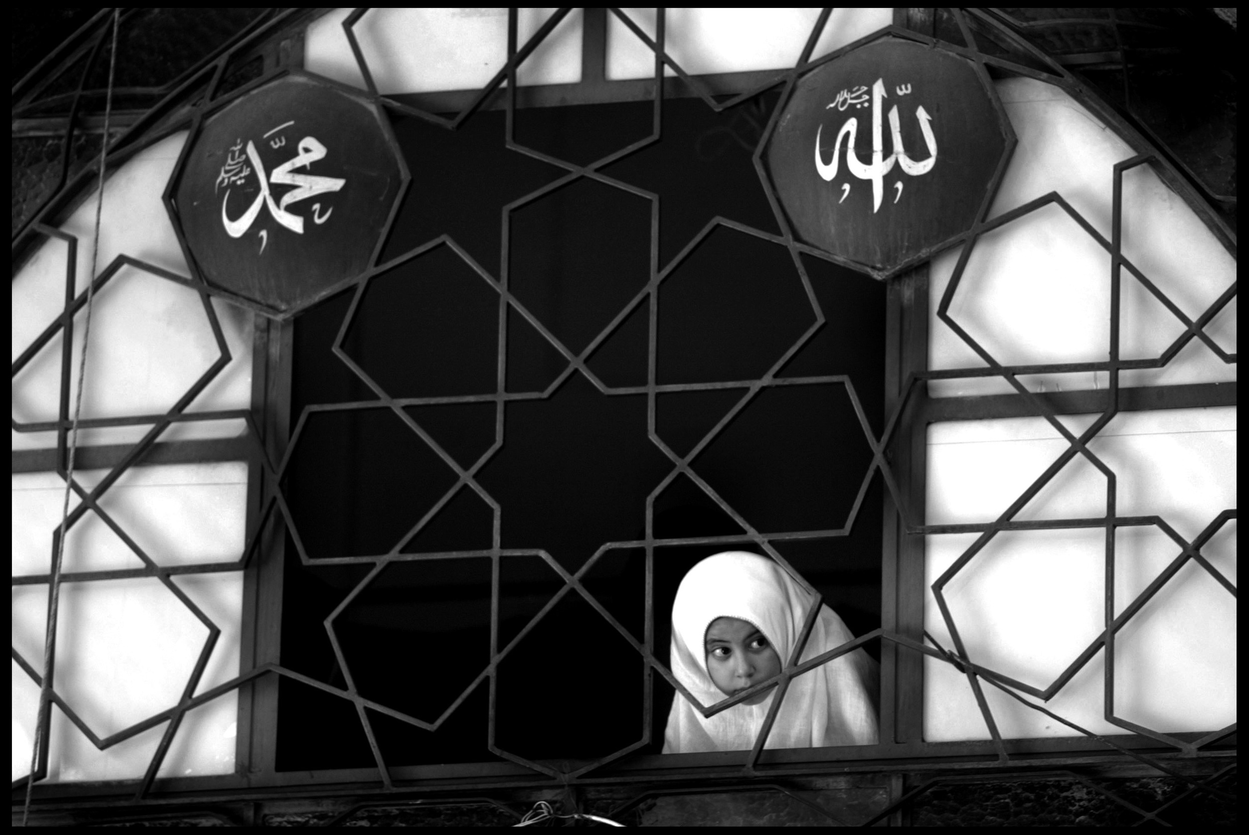 A girl peeks from the women's section, Sheikh Muhyd'din Mosque, Damascus