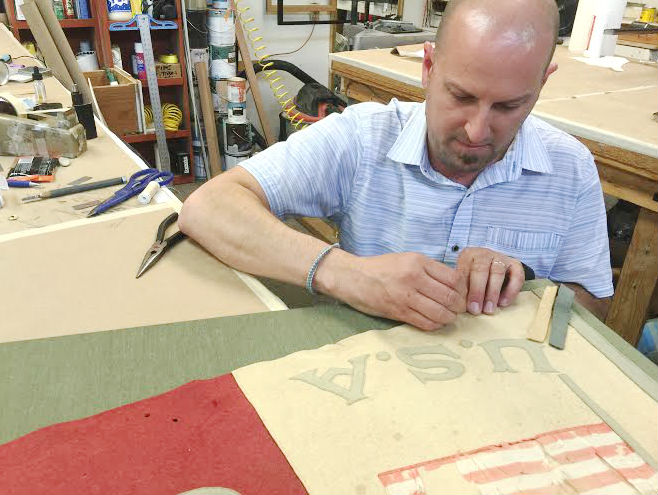"""Our framer/owner, Eric, hand stitched the 61.75"""" by 25.5"""" pennant to a hand-wrapped sea-foam green fabric mat."""