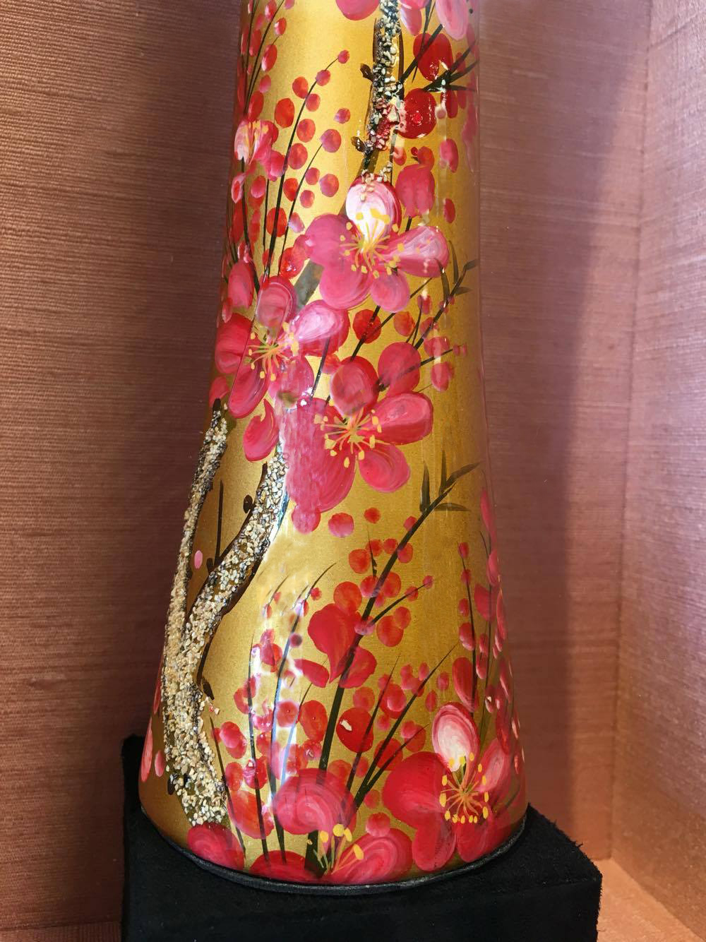 A close up of the vase's detail against the silk fabric.