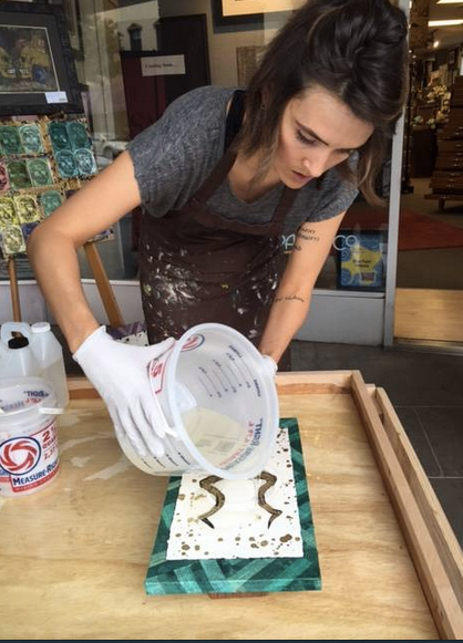 Kathryn Silvera coats a piece of artwork with resin during Open Studio Tours last year.