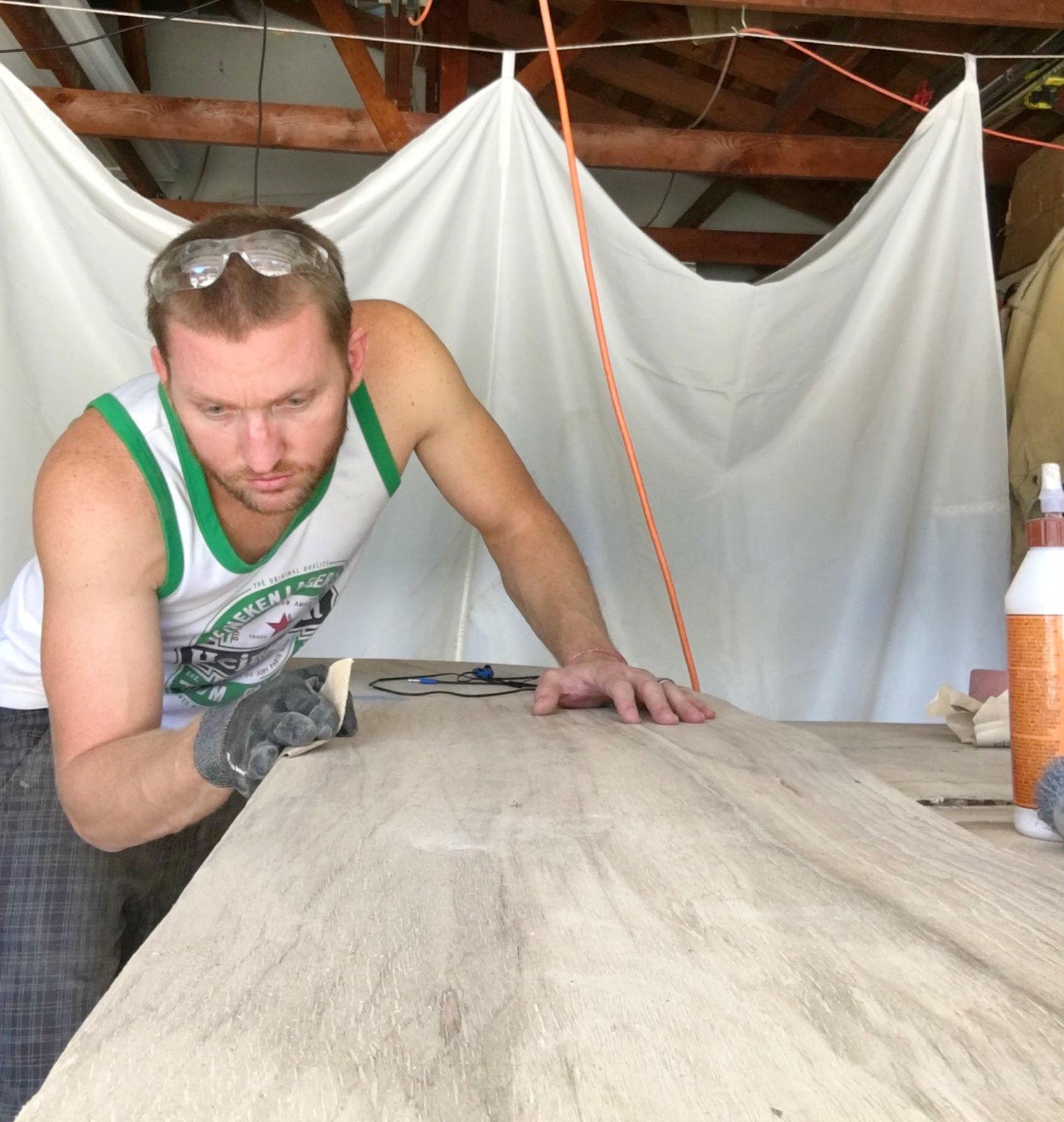 Kurtis Kruger sanding down the wood in his workshop.