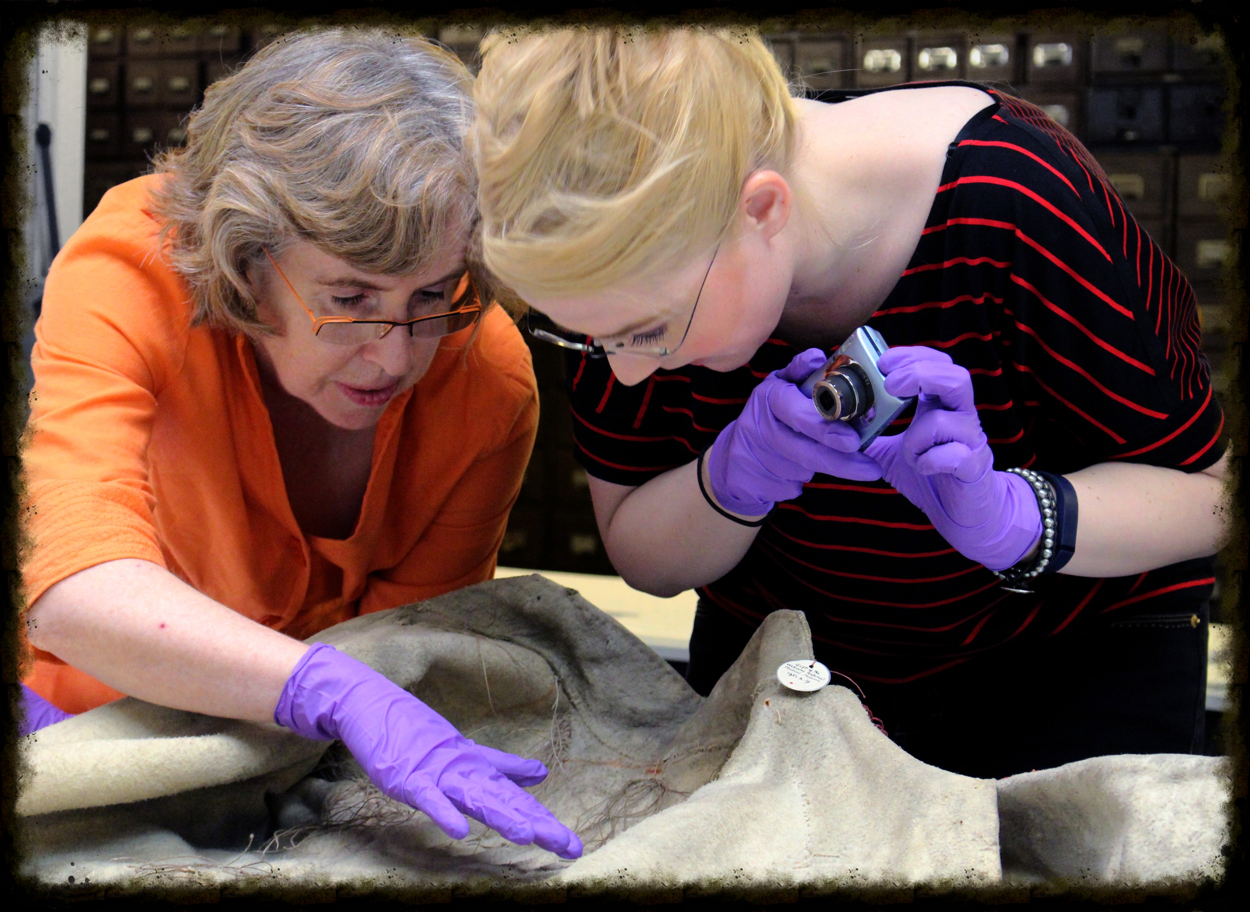 Susan Berry (left) and Katie   Pollock (right) identifying features on the Metis coat