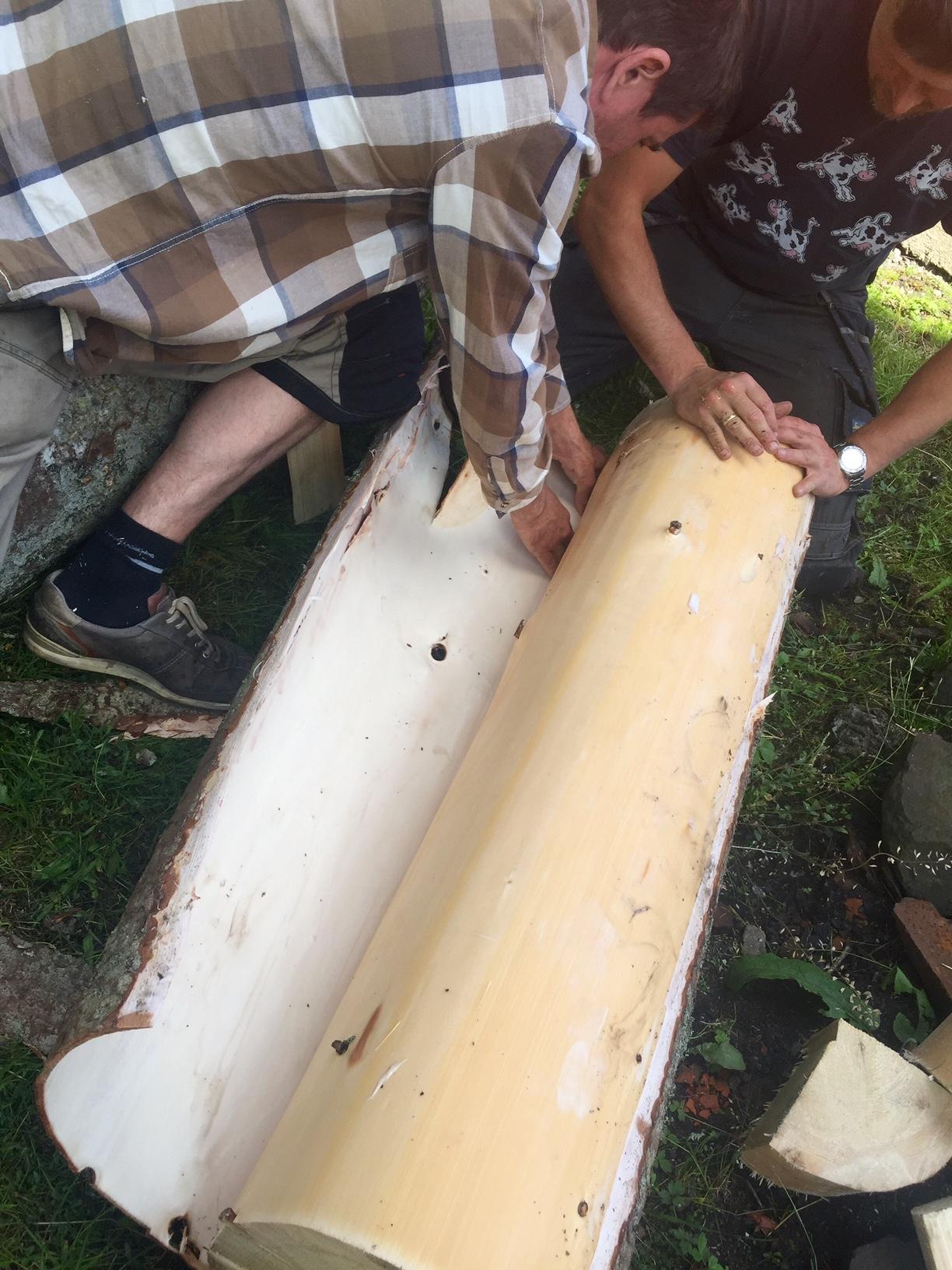 Arvid Sollie og Lars N. Løvdal fra Sollie Bygg tar av barken på en nyhøgd gran som skal brukes som takspon.