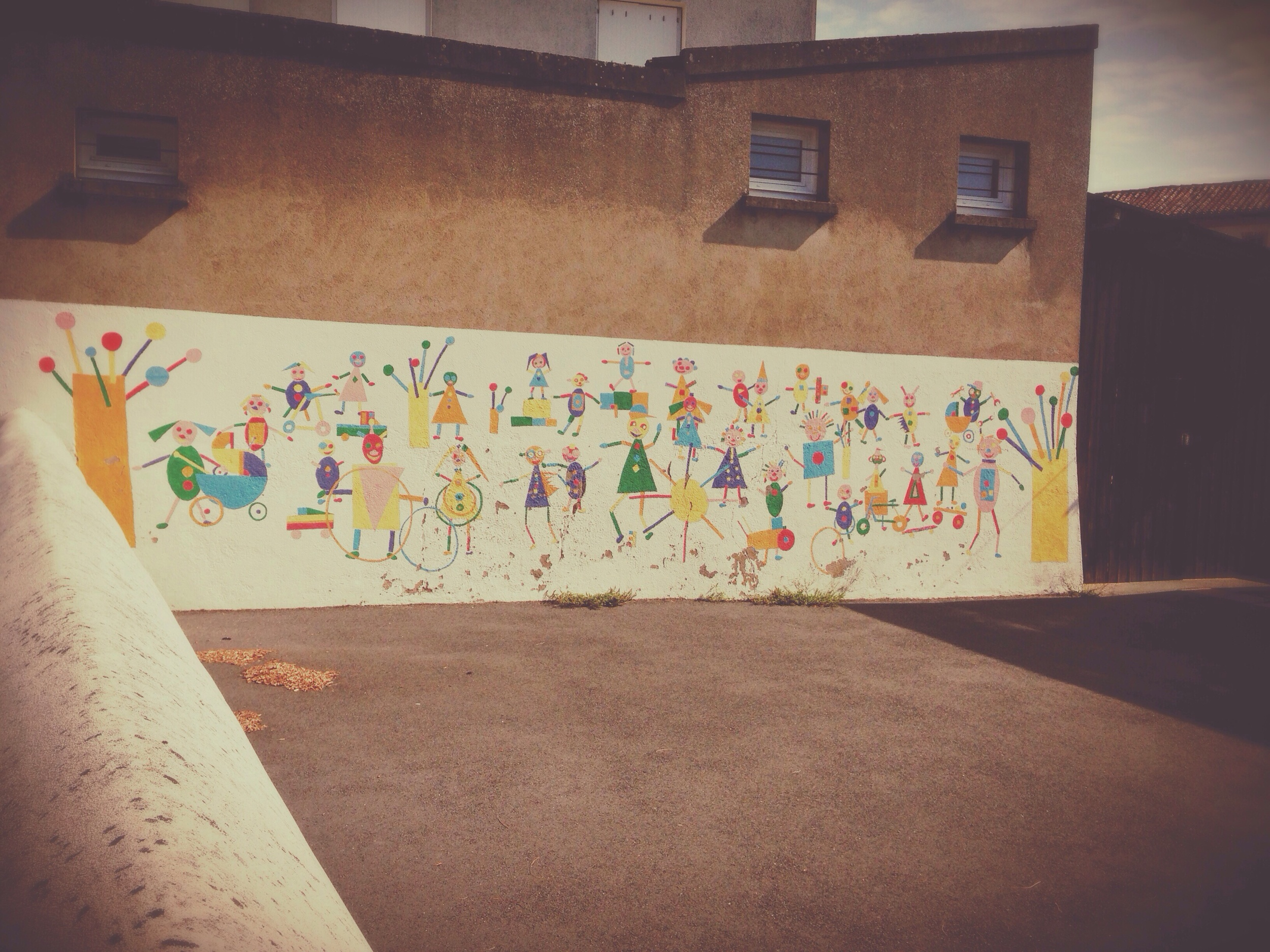 Preschool concrete yard with mural.