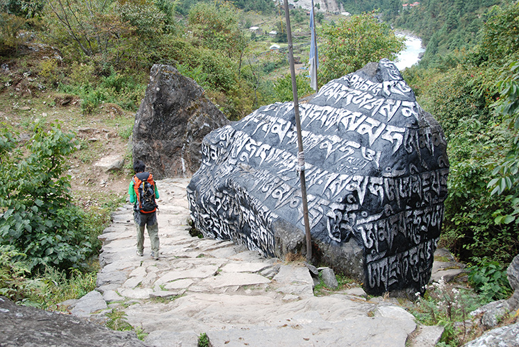Trailside boulder carved with Buddhist prayers