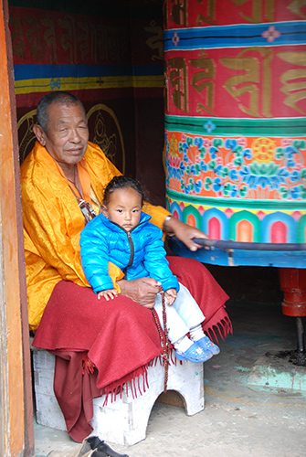 Sherpa and granddaughter turn a prayer wheel