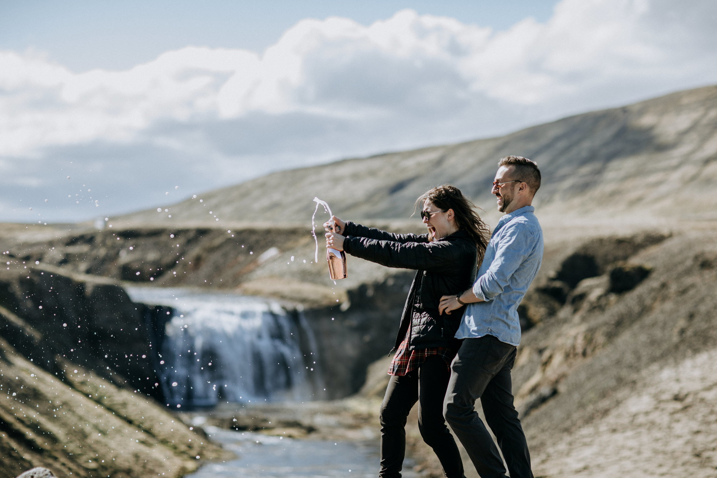 iceland engagement photo at waterfall champagne pop