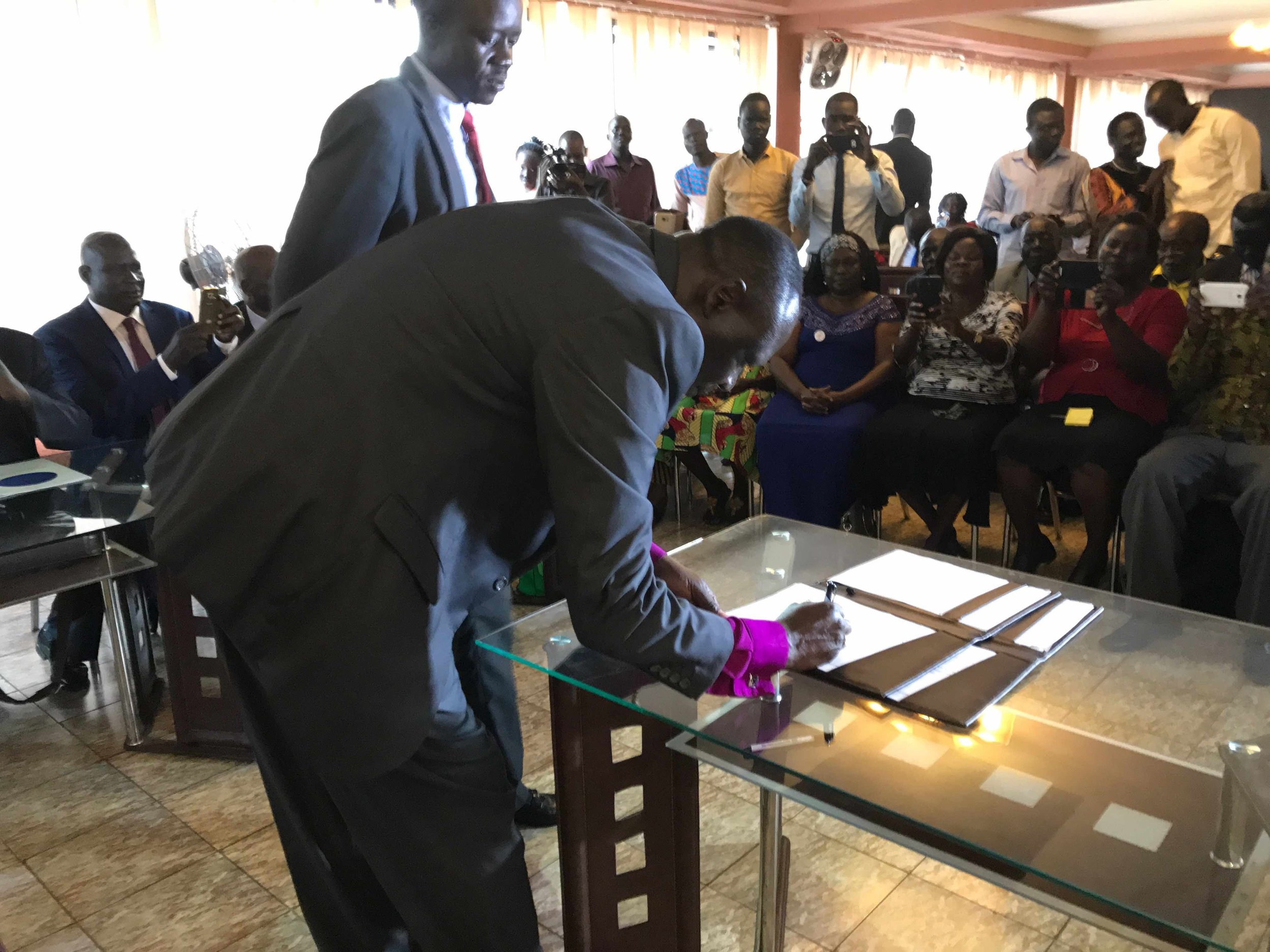 Bishop Taban signing the final documents after both signs have signed.