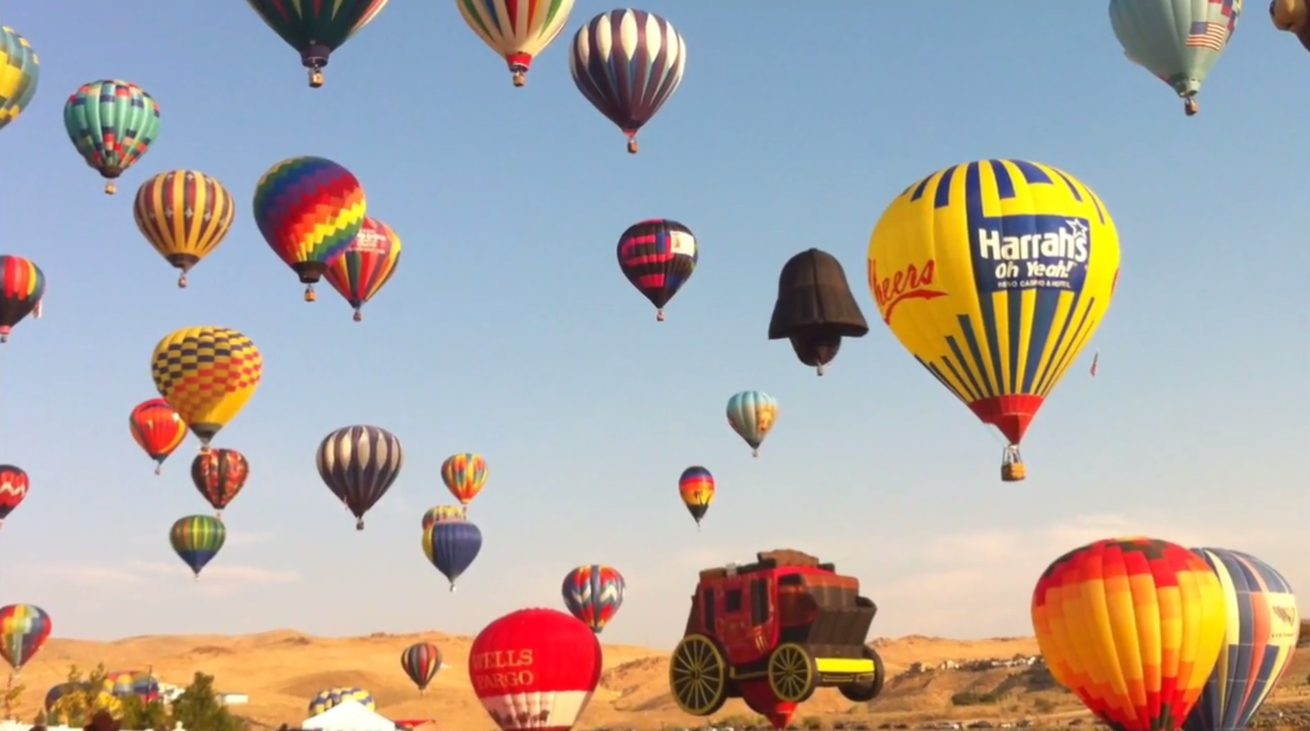 An array of hot air balloons lift beyond the Sierra Nevada Mountains to start the Great Reno Balloon Race. (2011)