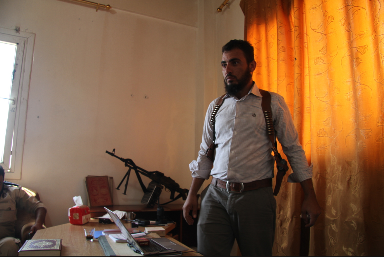 A rebel soldier stands by his desk at the Sham Falcons base in Bab Al Hawa, Syria. (2013,  The Guardian )