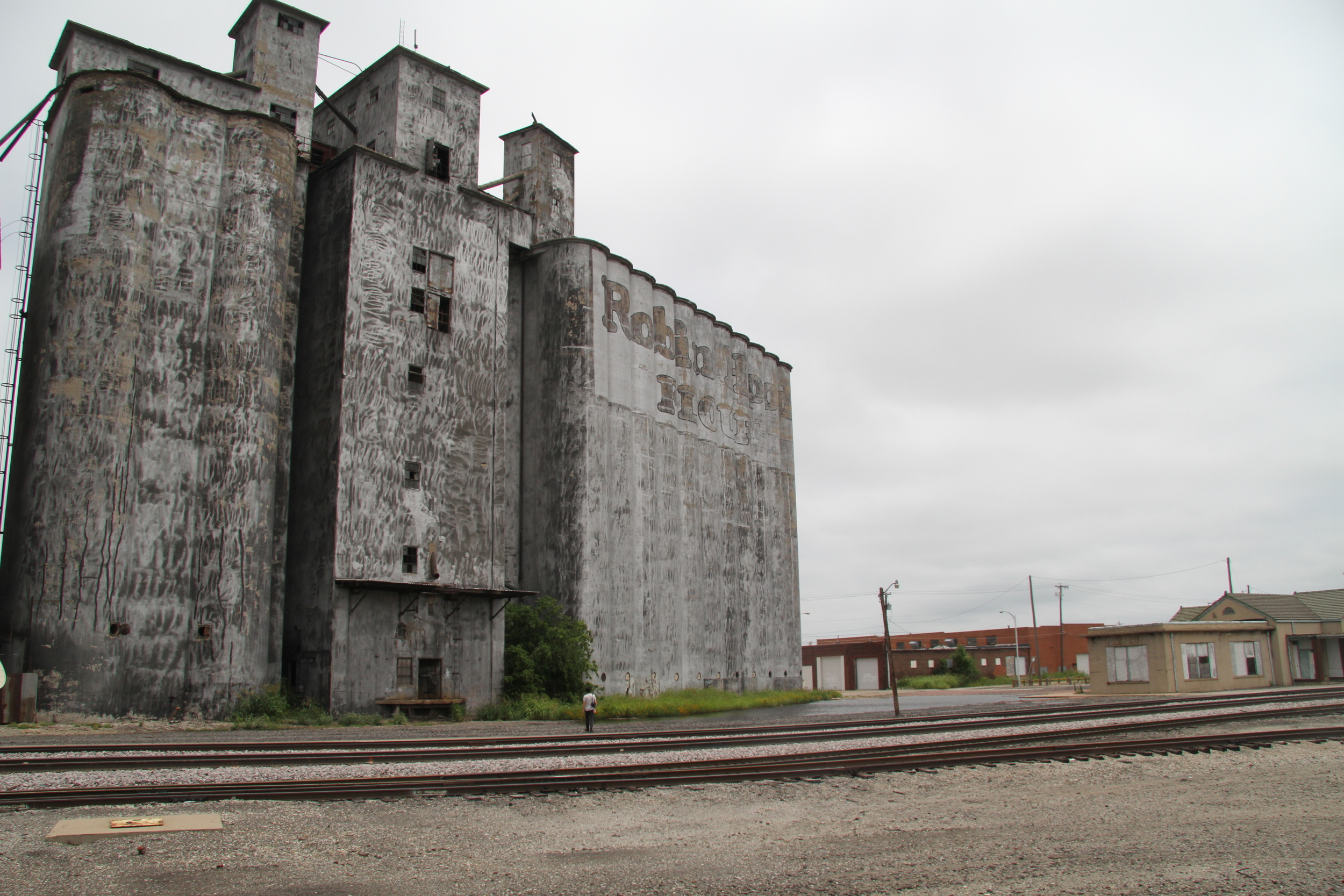 A visitor inspects an old Robin Hood Flour mill, now abandoned in Ponca City, Oklahoma. (2014)