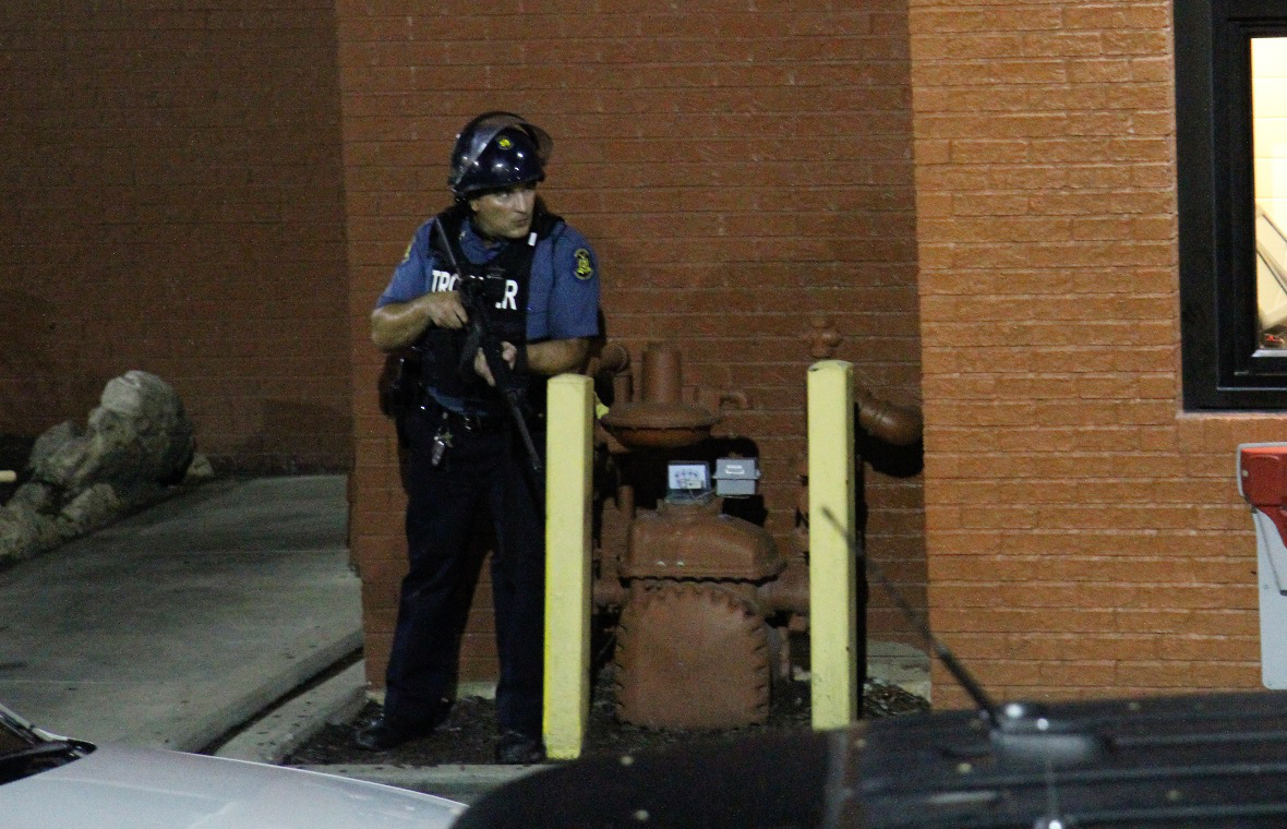 A police officer in Ferguson, Missouri observes demonstrations from a safe distance, gun at the ready. (2014, Medium)