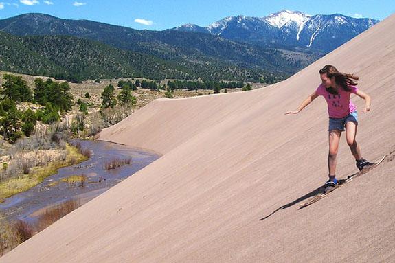 """Girl Sandboarding Above Medano Creek, Castle Creek Picnic Area"" by Patrick Myers"