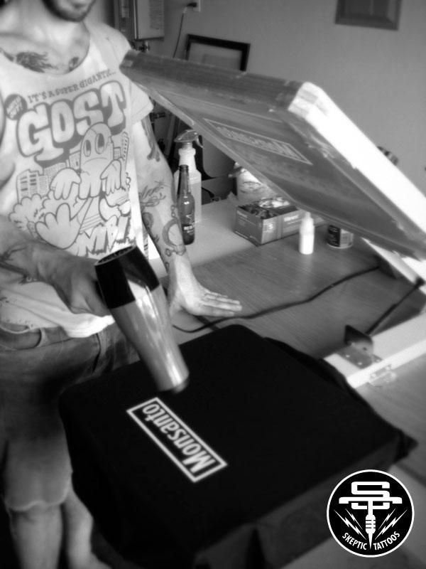 Arlo sweating in a garage, printing Monsanto T-shirts.