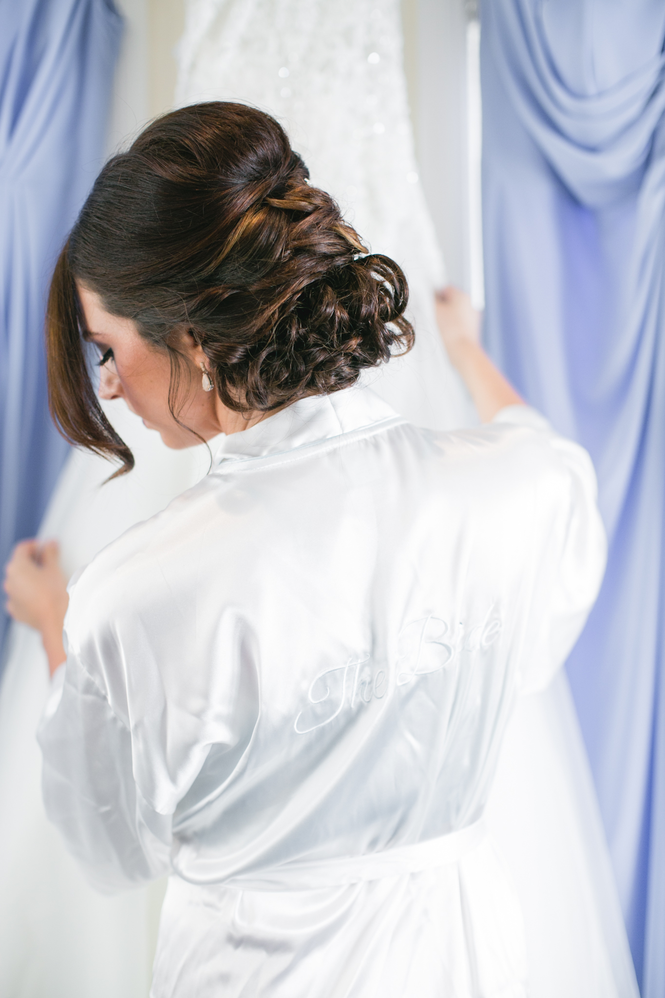 Stephenie getting ready to put on her dress. Also, love these bridal robes.