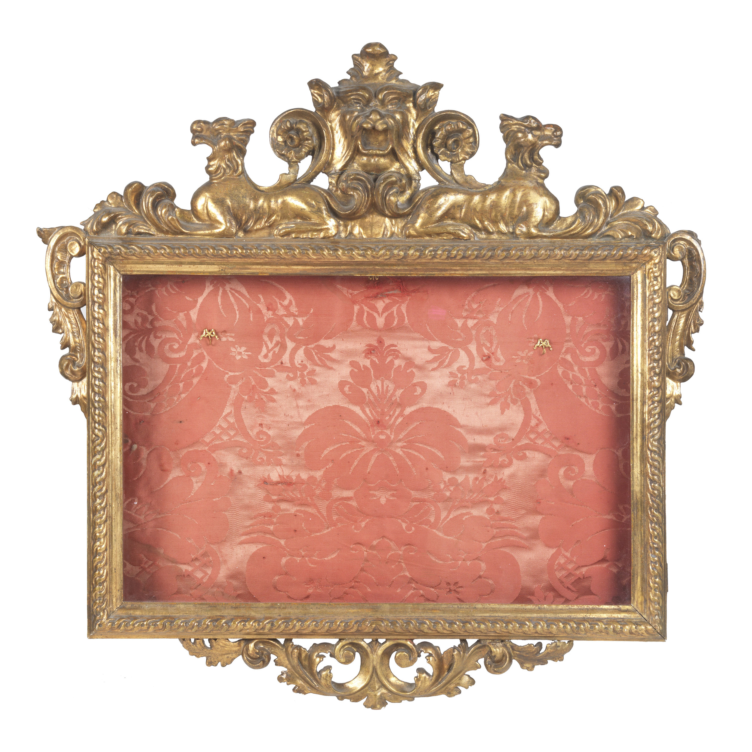 Early 19th Century glazed display case originally used to exhibit portrait miniatures. Carved wood and gesso frame and original gilding. The rope work frame features plumes and scrolls, and is surmounted with a pair of stylised hounds either side of the central grotesque. Lined with period red silk damask.  Sold