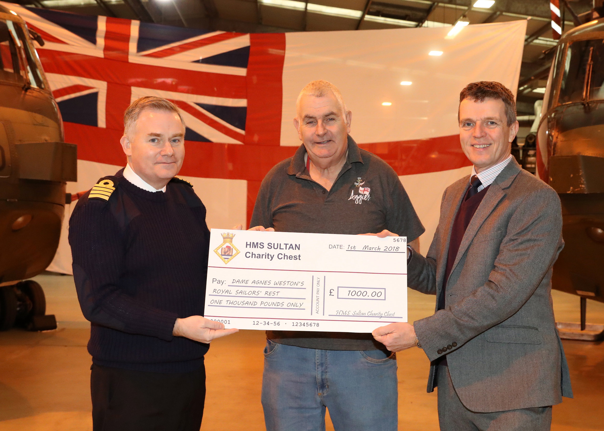 Captain Pete Towell from HMS Sultan presents a cheque to Steve Howlett, Aggie Weston's Pastoral Worker and Craig Fulton, Aggie Weston's CEO.
