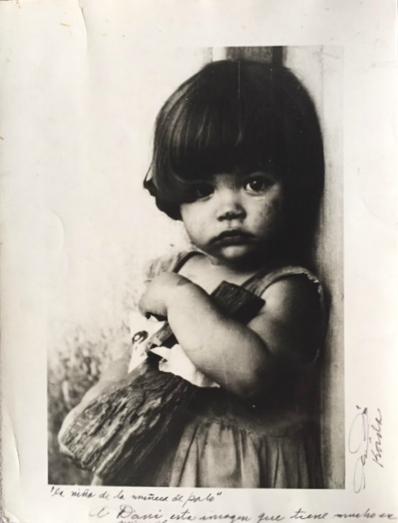 """Alberto Korda (1928-2001)   La Nina de la Muneca de Palo, 1959   Gelatin silver  Paper, 16 x 12""""  Image, 13 x 9""""  Inscribed and signed on front, bottom in black pen: """"la Nina de la muneca de palo."""" A Dani, esta imagen que tiene mucho en mi vida. Alberto Korda (The girl with the doll of wood. For Dani, this image that has much in my life. Alberto Korda)  Vintage"""