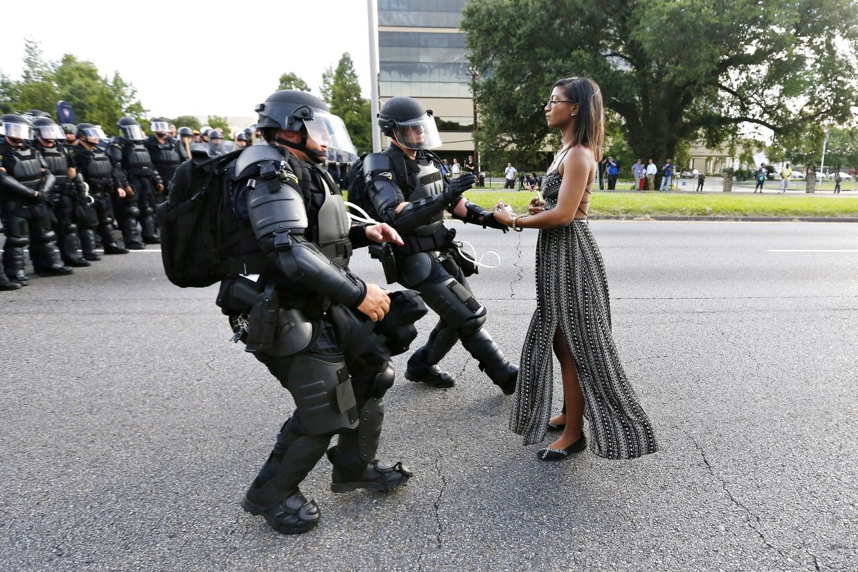 """Protester in Baton Rouge 2016 Jonathan Bachman (Reuters)  """"I photographed someone arguing with an officer and then I looked over my shoulder and saw her there and she had every intention of not moving,"""" Bachman  told  BuzzFeed News  . """"She just stood there and made her stand. I was just happy to be able to capture something like that.""""  The woman, identified as 28-year-old Ieshia Evans, stands in extreme contrast to the heavily-armored SWAT team members who are engaged in arresting her."""