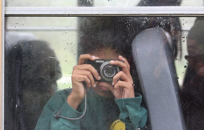 800px-Student_on_school_bus_holding_camera.jpg