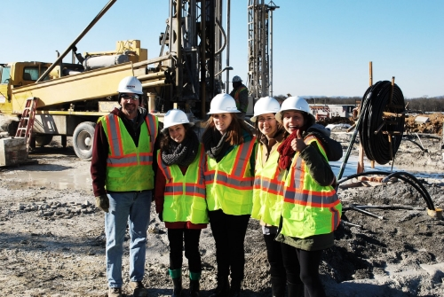 The Urban Green Labbers pose in front of some massive drills with Doug from Mid-State Construction.