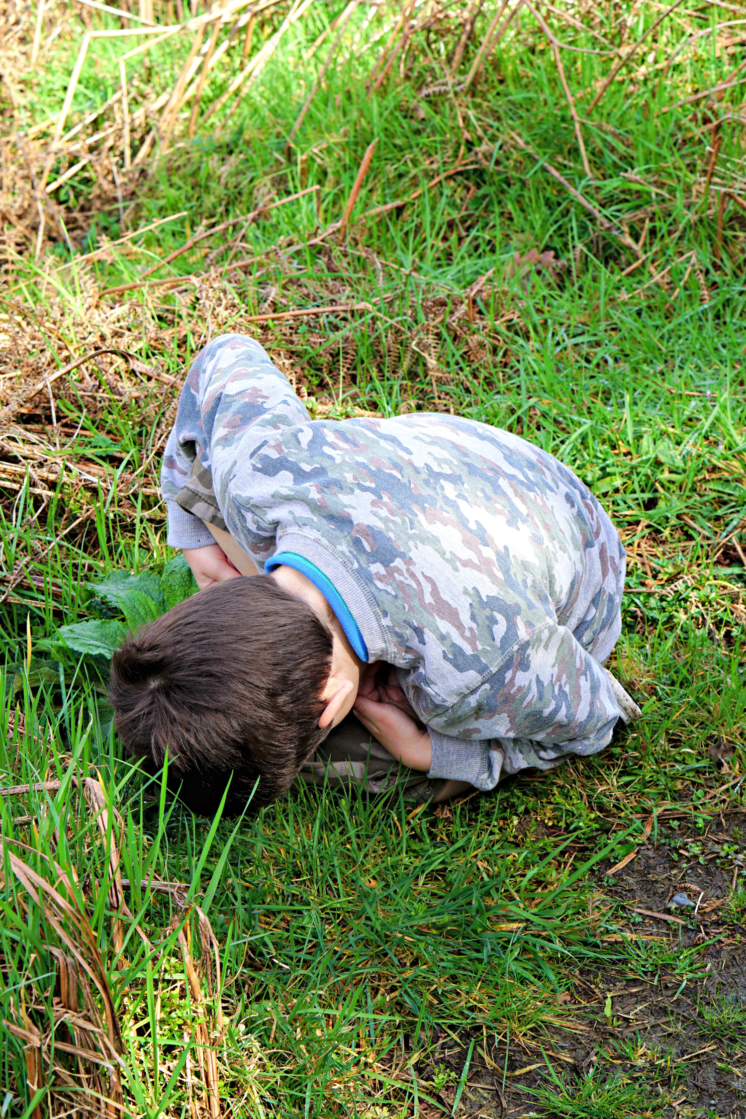This is a six year old's version of putting their hands over their eyes and thinking you can't see them. He's wearing camouflage so therefore invisible to the naked eye when curled up on the grass.