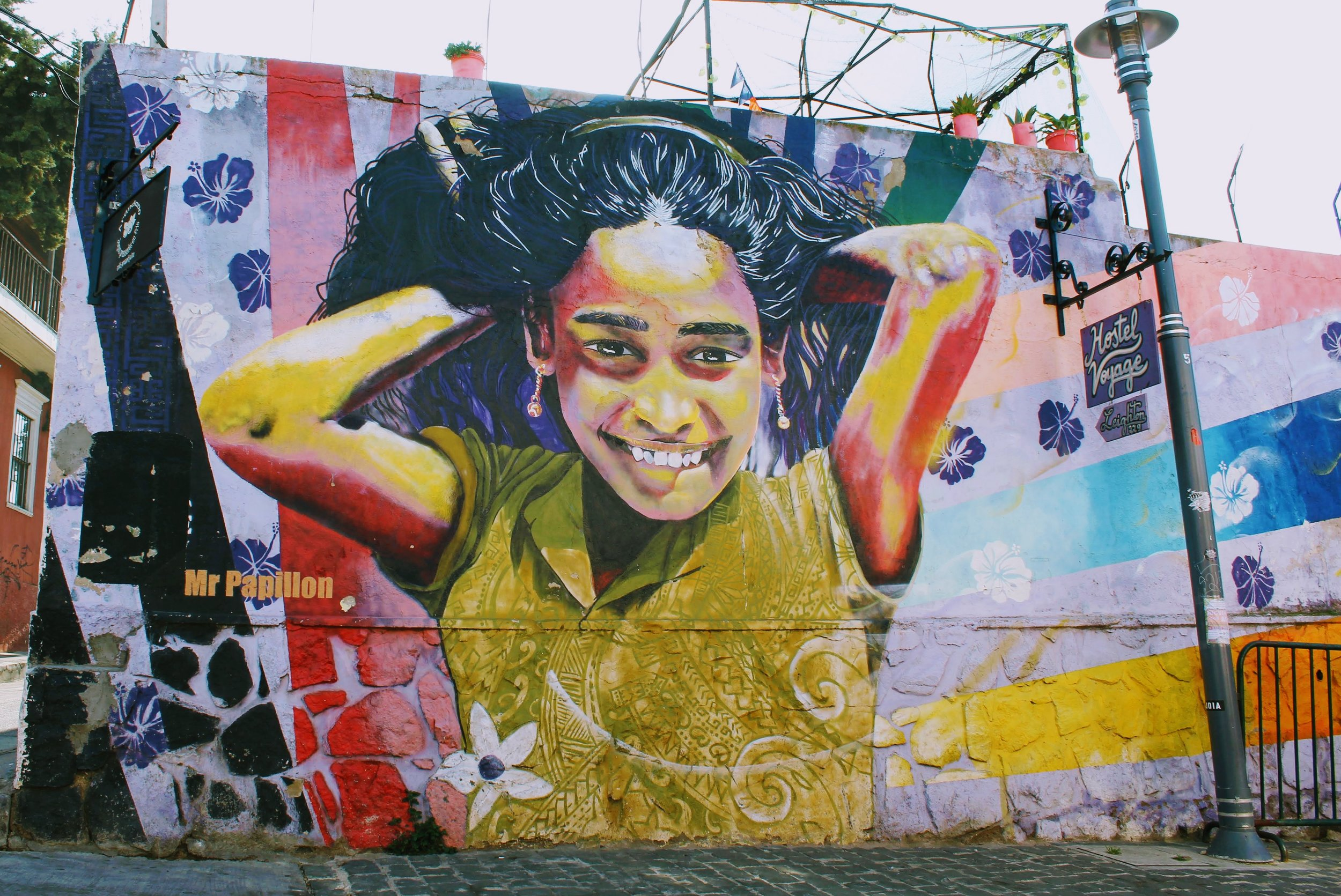 """Street art mural of """"Young Girl"""" by Mr Papillon for Hostal Voyage"""