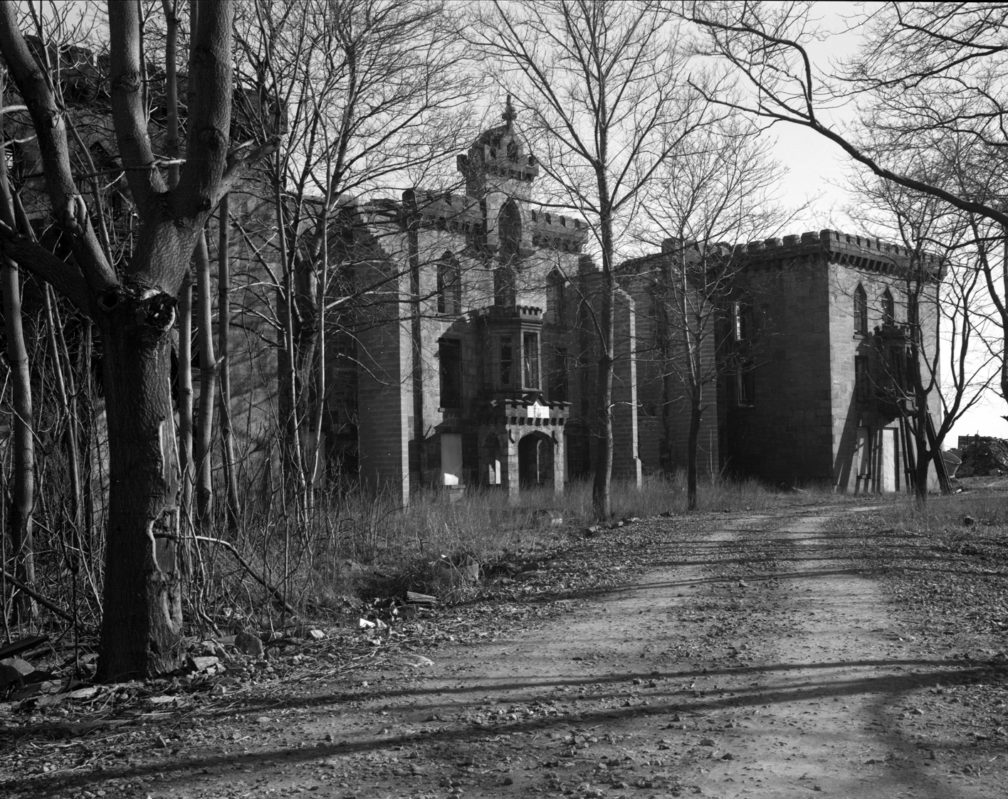 In 1976, the main façade of the Smallpox Hospital was more intact and the building was surrounded by many more trees, New York City Landmarks Preservation Commission