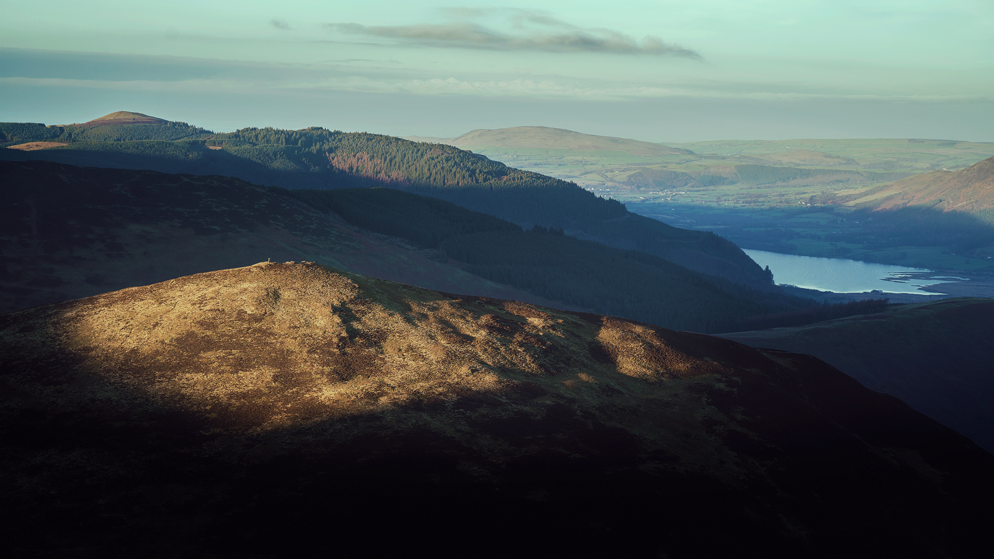 A walker atop Outerside, with Bassenthwaite in the distance.