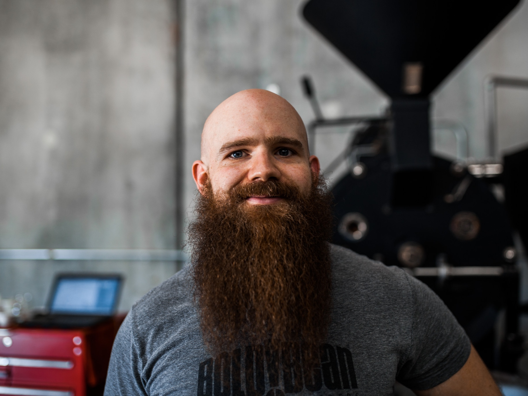 """Chris Rucker, Head Roaster   Coffee roasting plays an important role in our company. For many of us at Bold Bean, most things start as a hobby. The same goes for Chris. He says, """"I started working with coffee, just as a hobby, roasting at my house."""" Chris worked his way up from a Bold Bean customer to now managing our entire roasting operation. """"My job is to make sure everything that comes out of the roaster tastes excellent,"""" Chris Rucker says. """"The farmers give us quality green coffees to work with. It's my job to make sure I pass along quality roasted coffee to the baristas and wholesale accounts to serve our customers."""""""