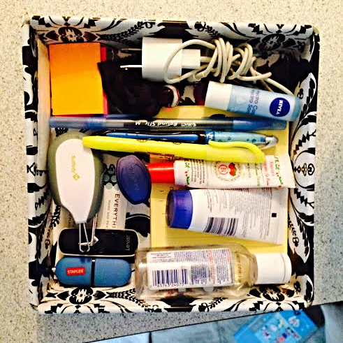 Keep the contents of the tray simple: a few pens, notepad, paperclips, elastics, hand sanitizer, etc