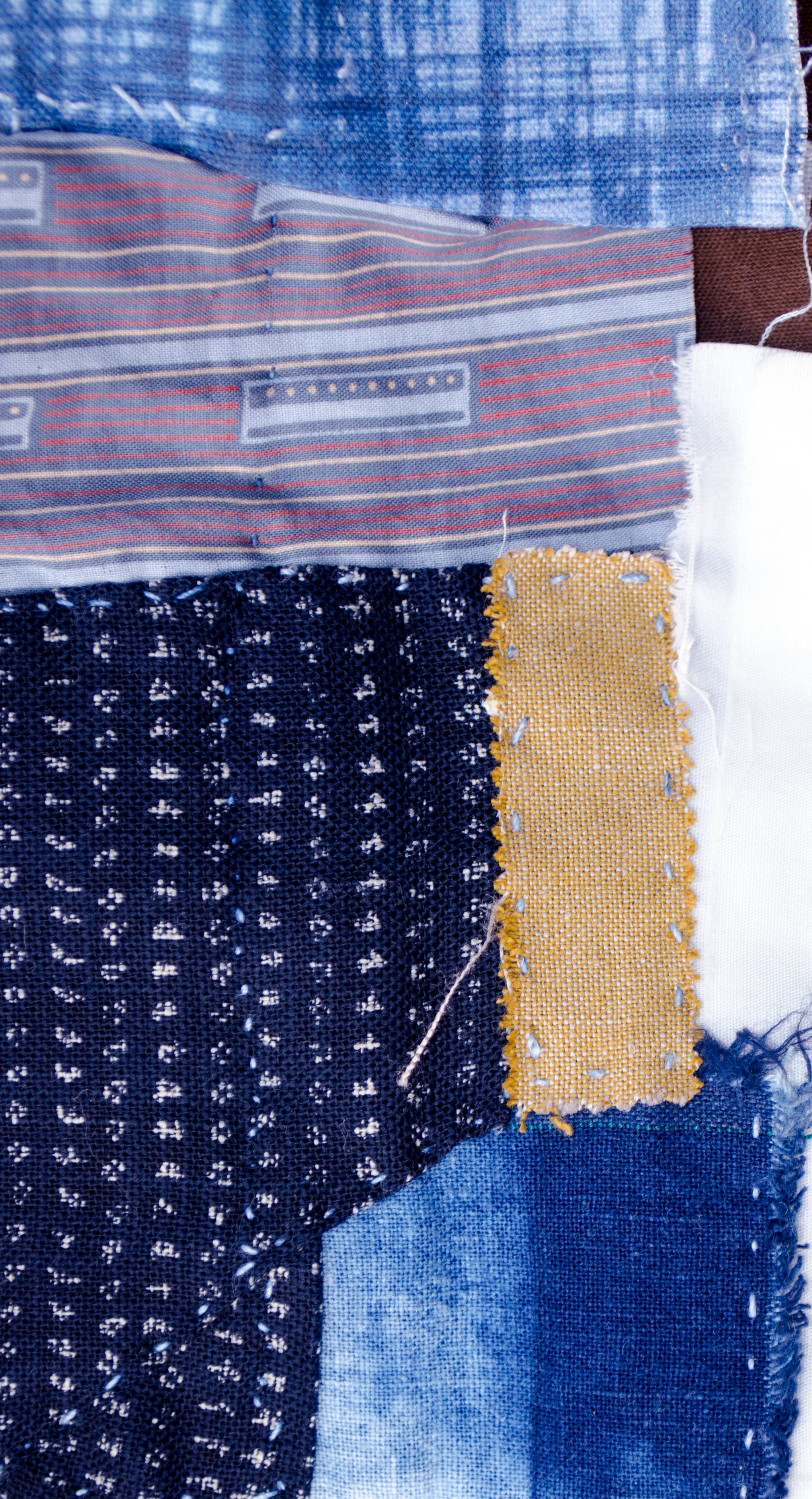 Bits of linen and cotton, shibori dyed and block printed stitched to patch an old jacket in the boro style