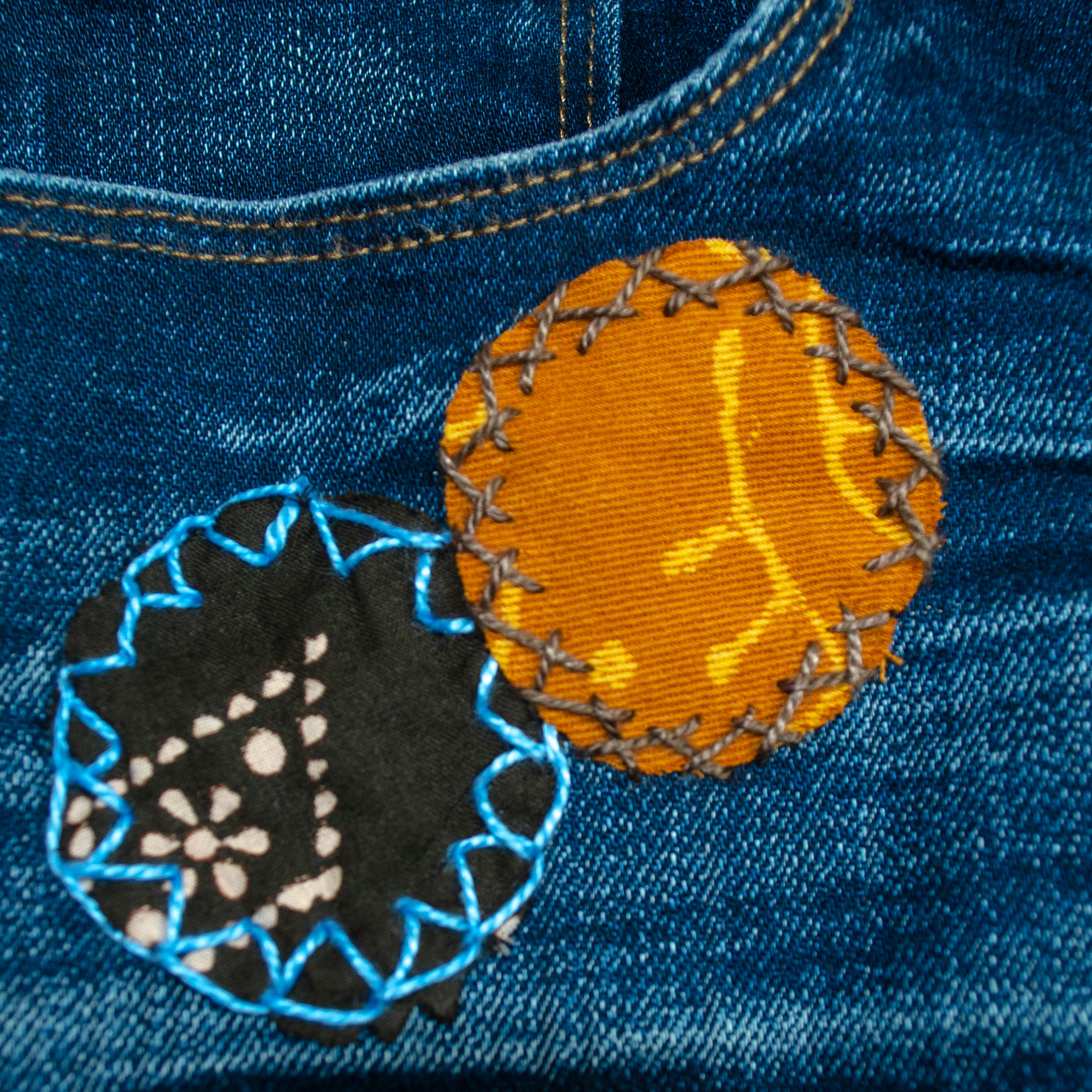 DMC Perle Cotton used to hand-stitch patches onto denim jeans. Decorative stitches highlight the visible mending.