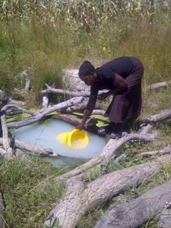 """Gathering water from the """"clean"""" water source in Mayoba, Zambia."""