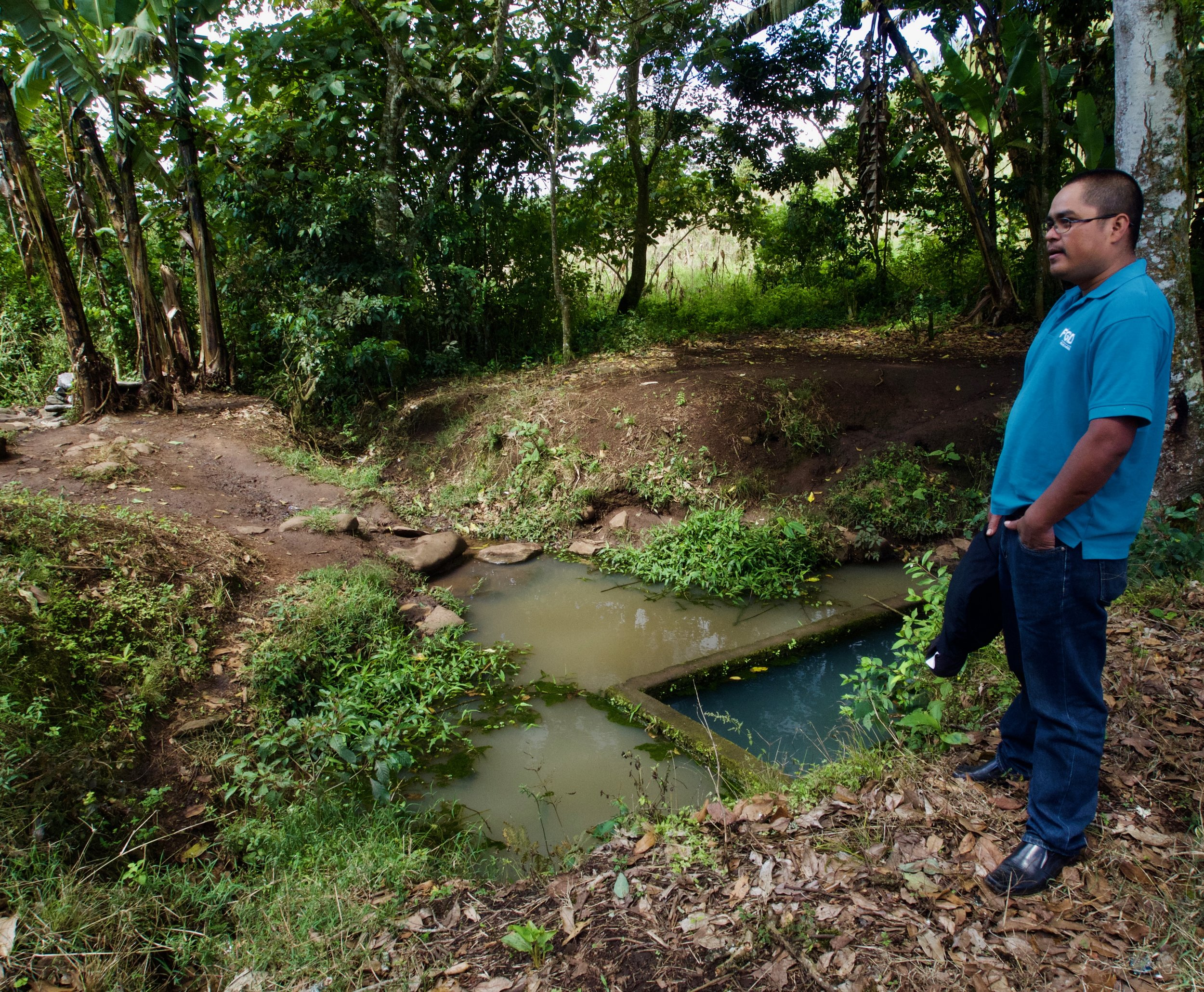 Community president Humberto stands next to the current, polluted water source in Yanque.