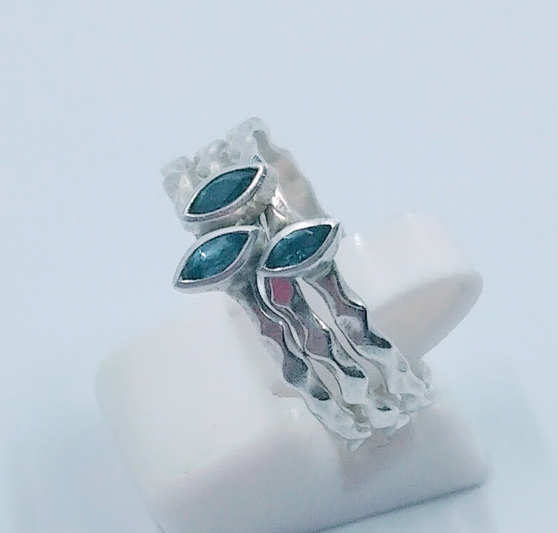 Set of three stacking, textured silver rings, each one set with a marquise-cut London Blue topaz