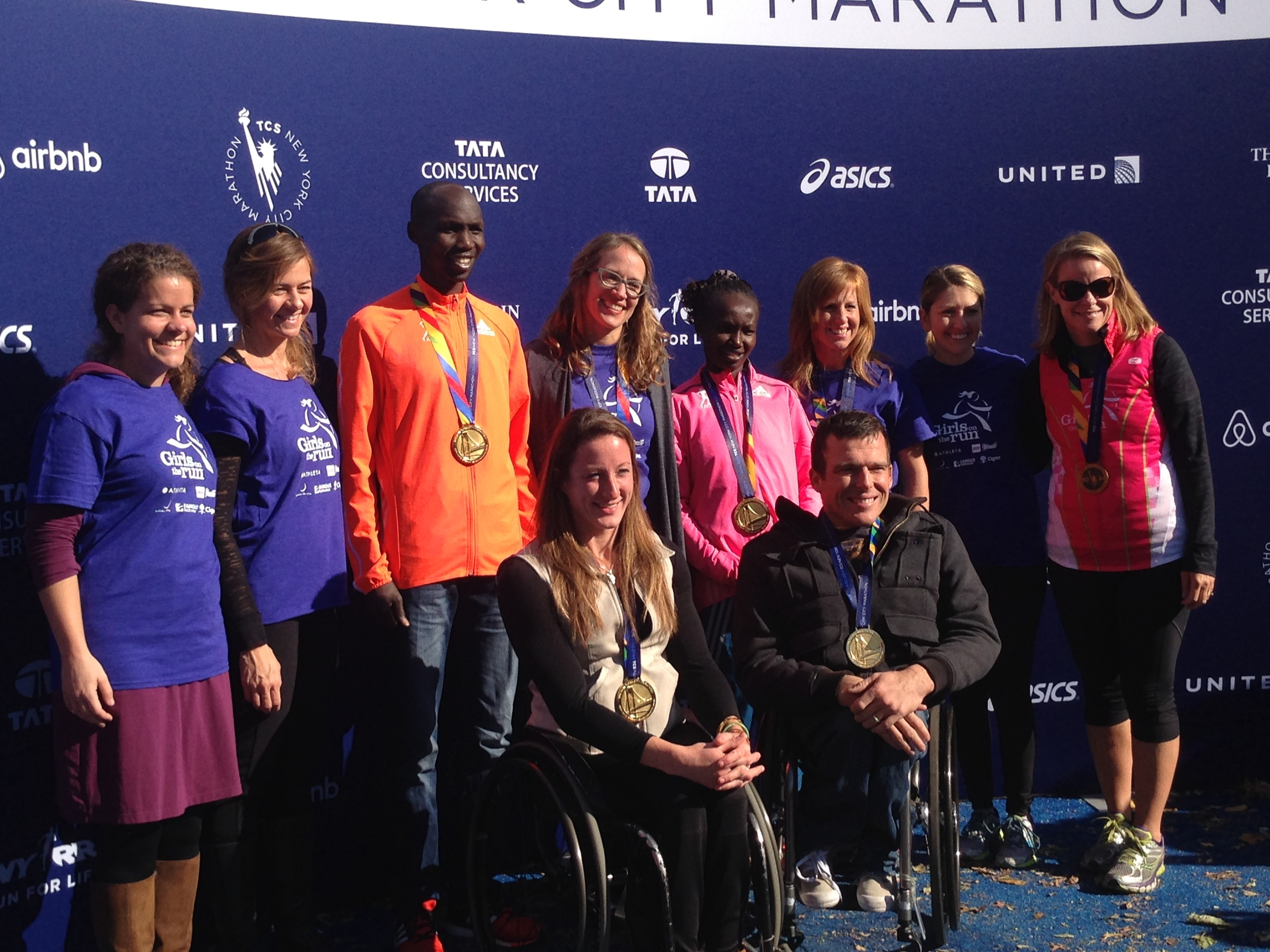 Girls on the Run NYC celebrates with the 2014 NYC Marathon Winners and our very own winner, SoleMate Katherine Slingluff - the one millionth finisher!  Seen here: Allison Hauser, Executive Director GIrls on the Run NYC; Stacy Lockhart, Coach; Wilson Kipsang, 2014 Men's NYC Marathon Winner, Katherine Slingluff, Millionth Finisher & Girls on the Run NYC SoleMate; Mary Keitany, 2014 Women's NYC Marathon Winner; Lara Mish, Girls on the Run Chesapeake Council Director; Gloria Mullervey, Girls on the Run NYC SoleMate; Tatyana McFadden, 2014 Women's NYC Marathon Wheelchair Division Winner; Kurt Fearnley, 2014 Men's NYC Marathon Wheelchair Division Winner