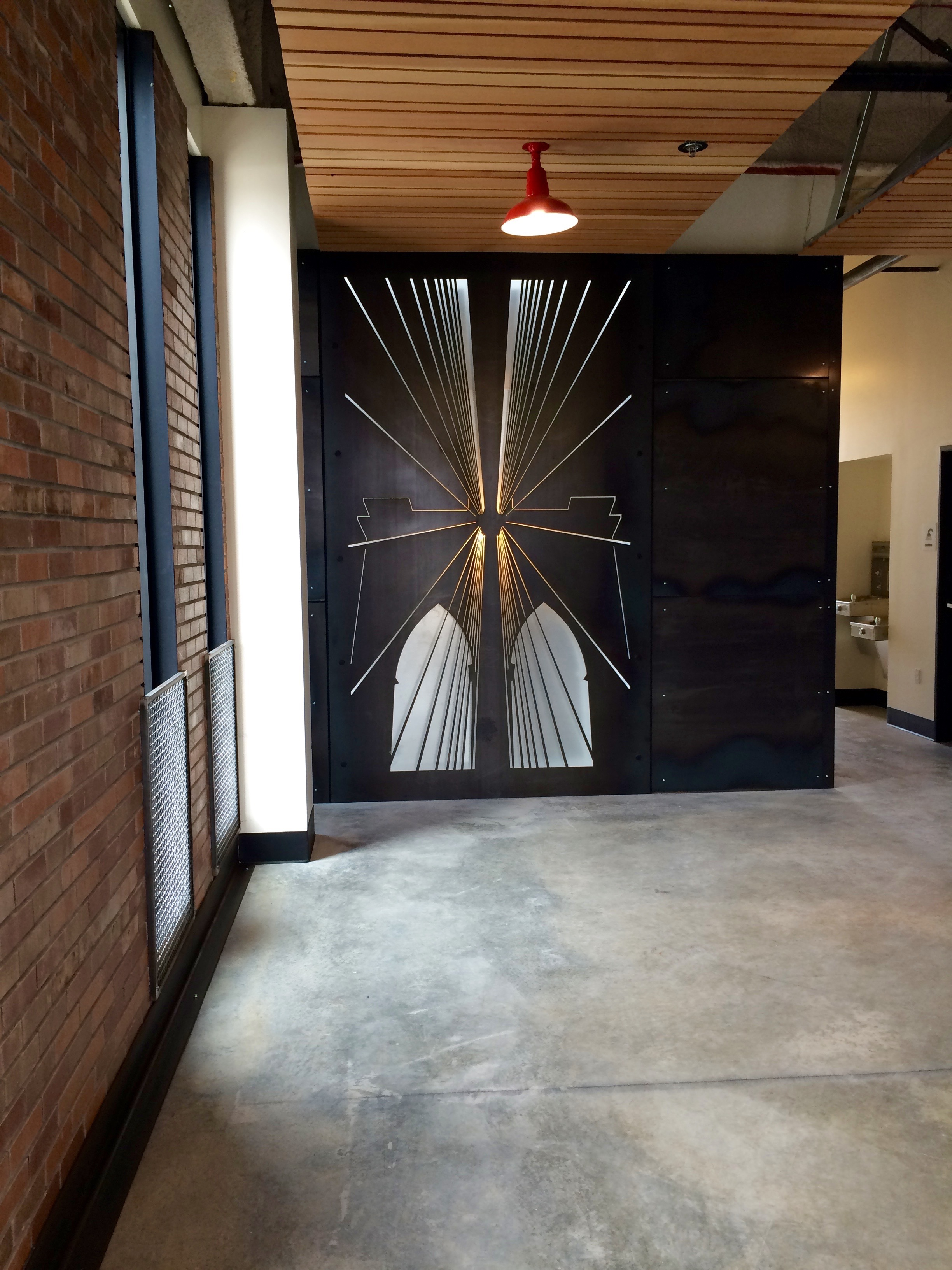 Public art fixtures of cut steel with backlighting adorn each floor.