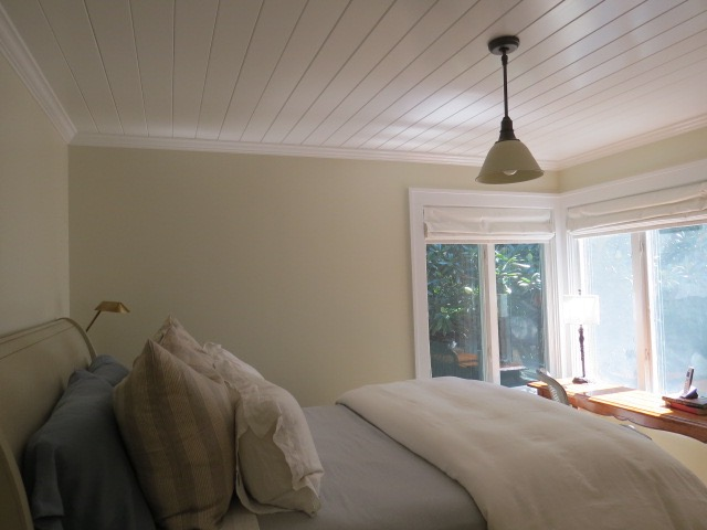 The second bedroom, the smaller, yearned for something a little different. This bedroom faces the back of the house with its little herb garden, and slate patio enclosure. The room seemed to beg for a contrapuntal statement, a place of peace all its own yet somehow more grounded in earth tones. After painting a lumber yard's worth of small wood squares with all manner of kindred colors, all from Farrow & Ball, I came up with the funnily named Clunch, a hue that harkens to an old world feeling of weathered parchment, yet with a modern character. It's both restful and has a touch art house cool. I wanted some texture too, so I had the ceiling done in wood plank, each about 4 inches wide, then painted them, you guessed it, All White, to lend the ceiling and trim the same glossy counterbalance to the elegant whimsy of Clunch. It works so well that the room looks both modern and ancient; it's become both writing room and a wonderful place for naps for anyone who needs one. Libeco bed linens stand out in pale relief to the saturated wall color, and a satin-white glass lamp overhead makes a lovely compliment, on or off.