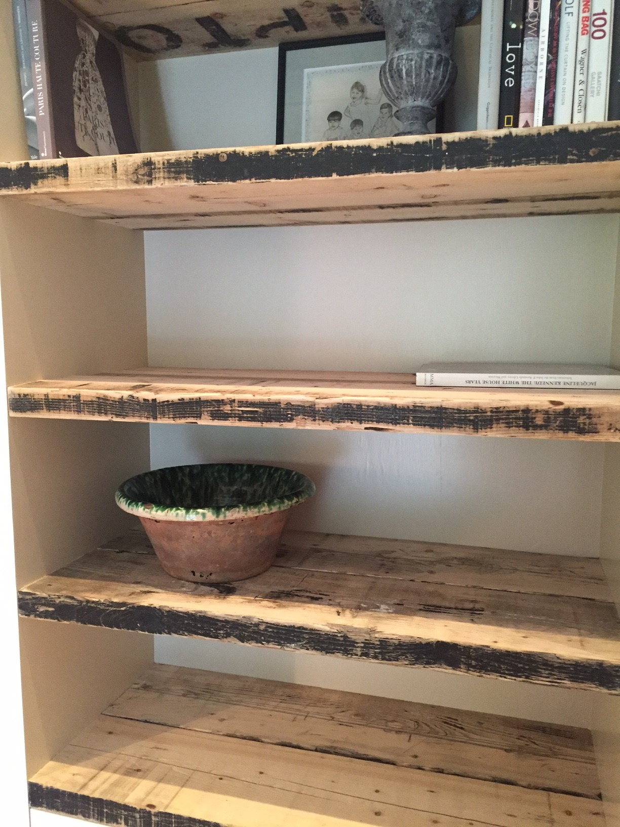 Custom bookshelves in the living room, done with thick, strong barn wood that had streaks of old black paint on them, were painted on the inside walls with Joa's White, a perfect compliment to the wood and the black. It gives a feeling of warmth and color to the thick sturdiness, a subtle depth to the bookcases. Since my business involved fashion, I have used these shelves as a wonderful atelier's holding area for knitted garments during my seasonal showcases.