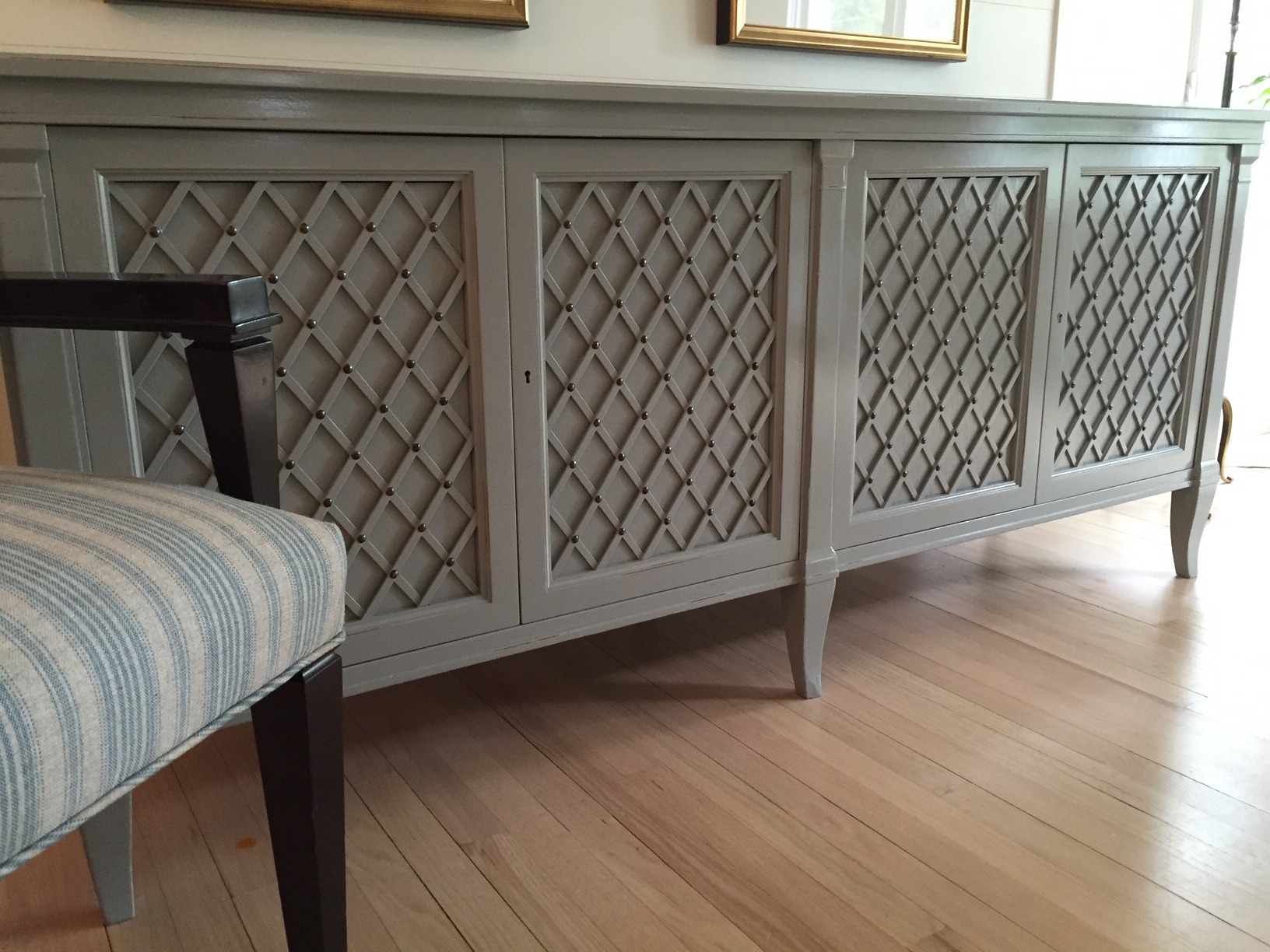 I had an old mahogany credenza with sliding lattice doors that looked right out of the fifties, and indeed it had been handed down for three generations, grandma to mother to me. It reeked of stodginess when placed in my All White living room, but as heavy and musty looking as it was I couldn't part with it. So I decided to paint it with Farrow & Ball's deep and lovely Manor House Grey, a color that looks striking against white and fits nicely with other furniture in beiges, blacks, browns, and color. The piece now gives the room a modern cool, a kind of industrial chic. Candlesticks, vases, books, anything I put on it pops with its own character now. Aged brass pulls compliment the cool with just the right touch of age and history.
