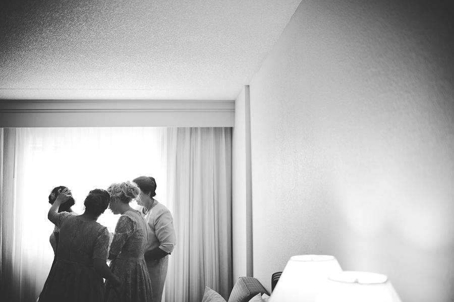 bridesmaids lacing up a wedding dress