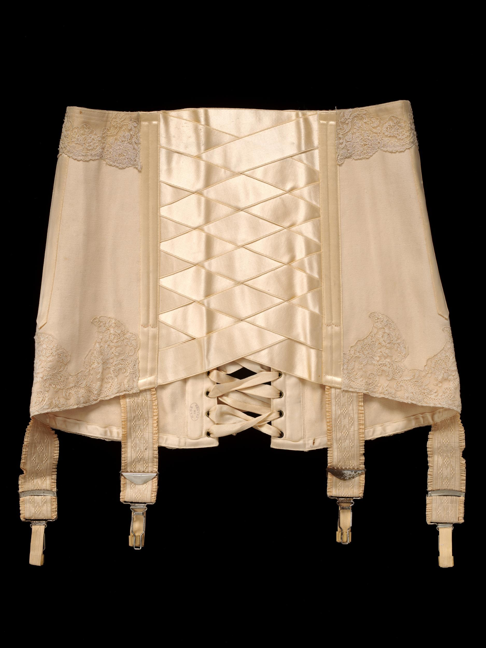 TANGO CORSET   - Cotton, Silk satin ribbon, Machine lace, Metal circumference / ca. 1914 France, for  Debenham & Freebody , London (V&A:T.64-1966) * Size  - waist: 67cm / hip: 88cm / Length front: 25cm / back: 33cm  Worn and given by Heather Firbank