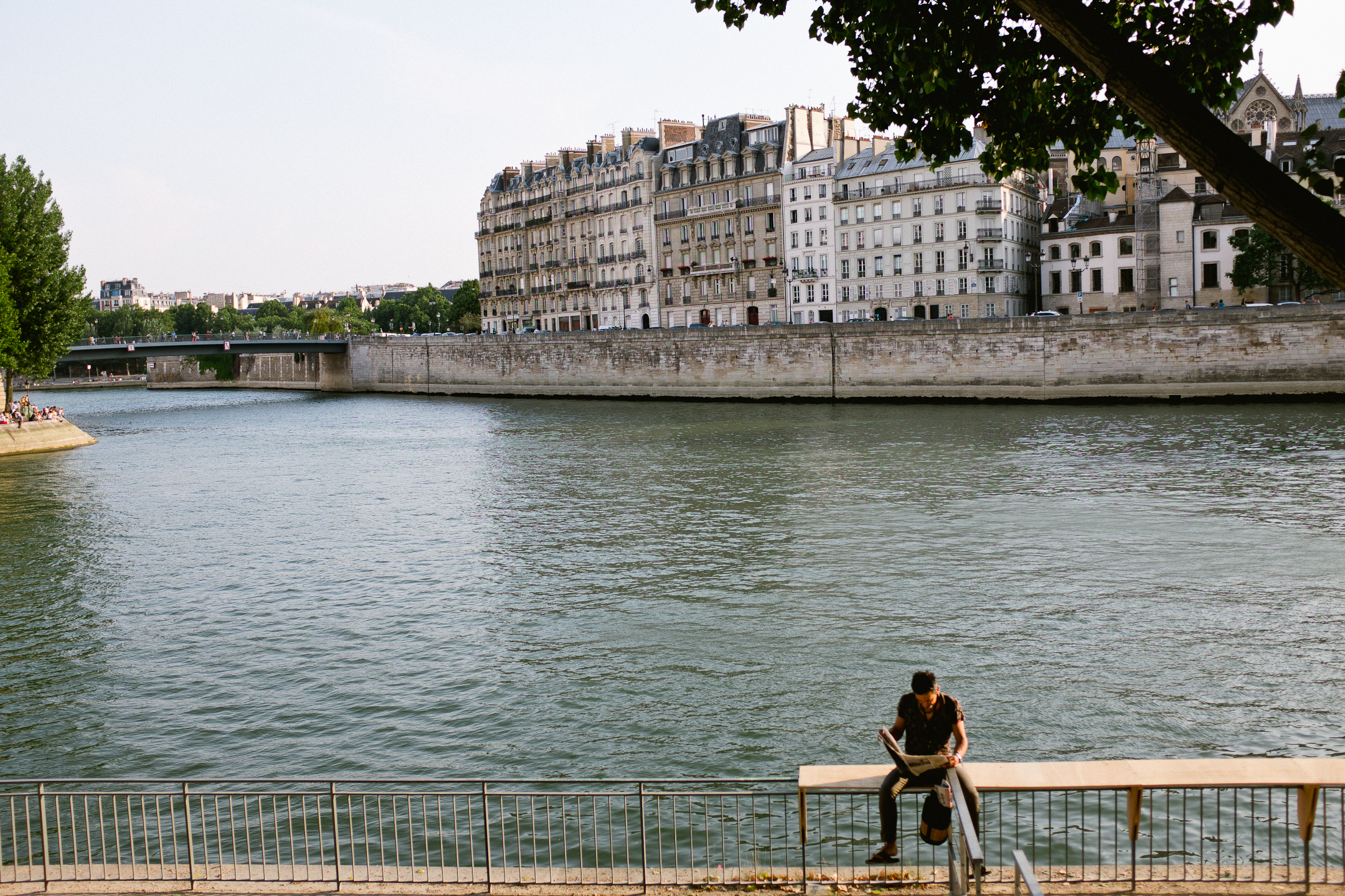 Reading the paper along the Seine in    Paris, France by Seattle based photographer Dylan Priest