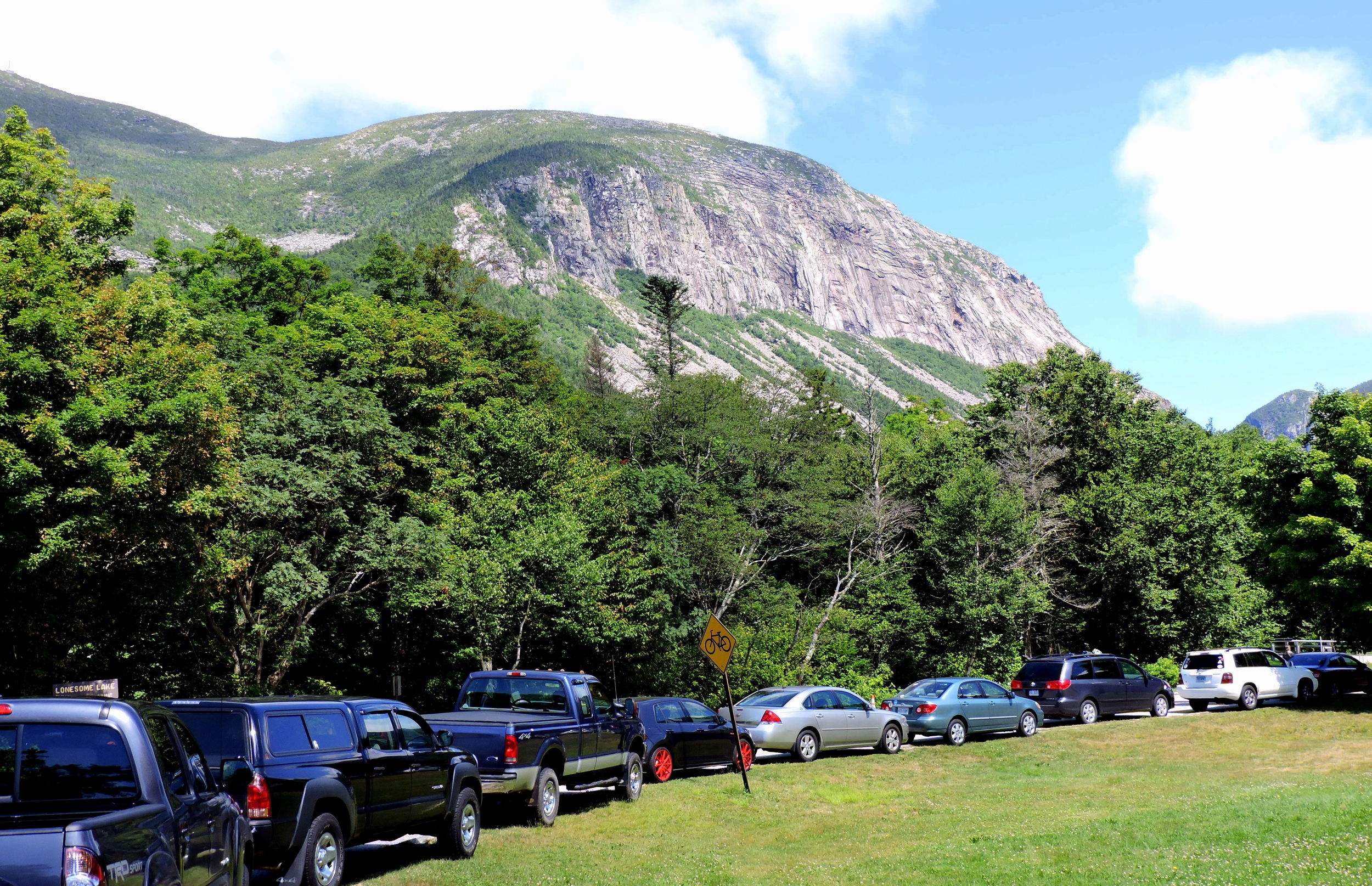 Cars parked along the entryway of the parking area for Lonesome Lake demonstrate the popularity of the area.