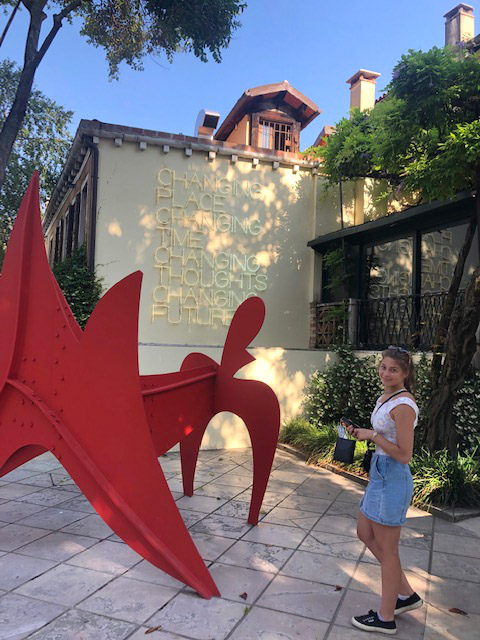 Outside Palazzo Venier dei Leoni with two works: Alexander Calder's bright red, painted steel sculpture  The Cow (La Vache) , 1971; and Maurizio Nannucci's  neon tube wall piece,  Changing Place, Changing Time, Changing Thoughts, Changing Future,  2003.