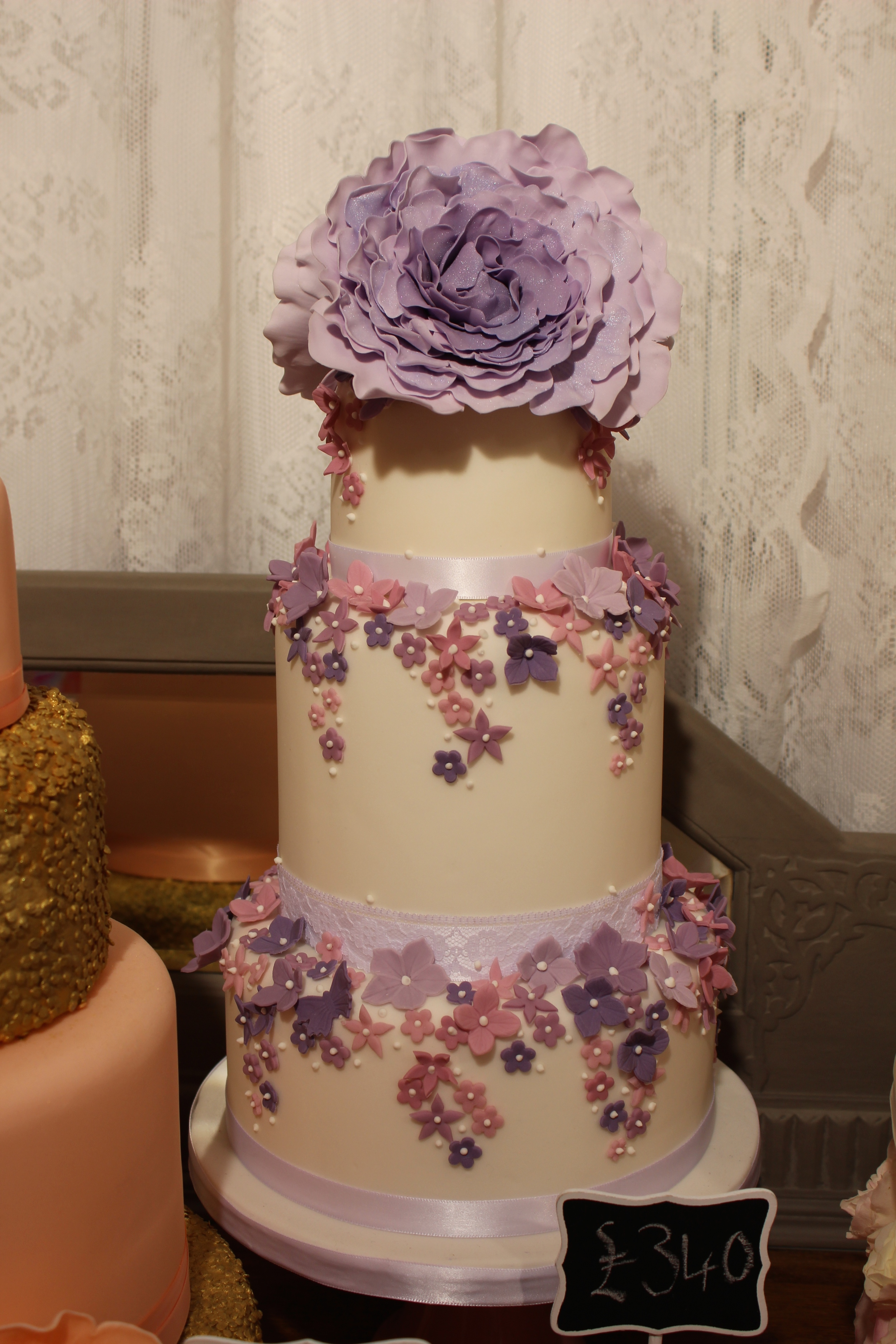 Purple and pink 3 tier cake with open peonies