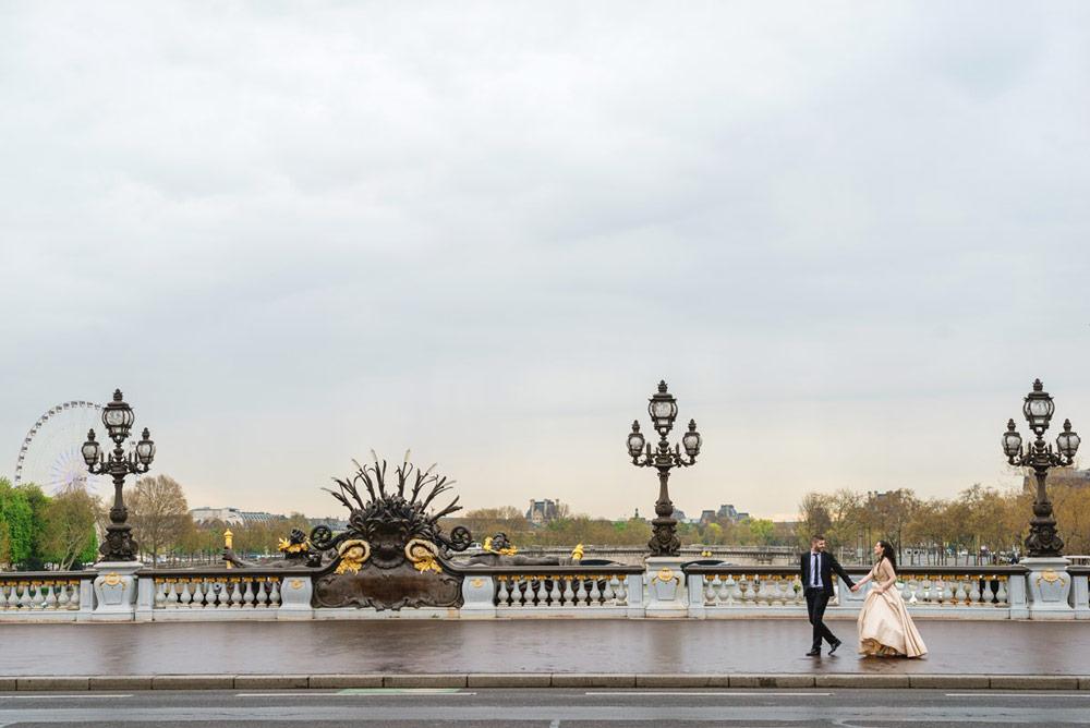 Paris-photographer-paris-for-two-Christian-Perona-wedding-proposal-love-Seine-quay-Alexander-III-bridge-golden-statue-wedding-dress-rainy-cloudy-day-walking.jpg
