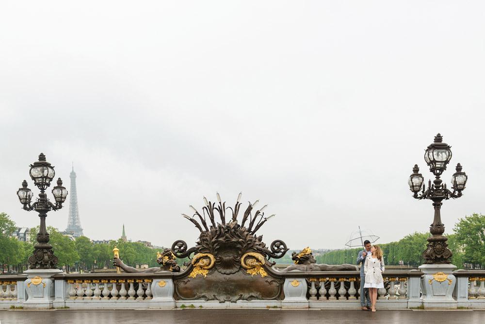 Paris-photographer-Paris-for-Two-Christian-Perona-professional-engagement-proposal-pre-wedding-portrait-Alexander-III-bridge-sunrise-rain-rainy-day-transparent-umbrella-Eiffel-tower-golden-statue.jpg