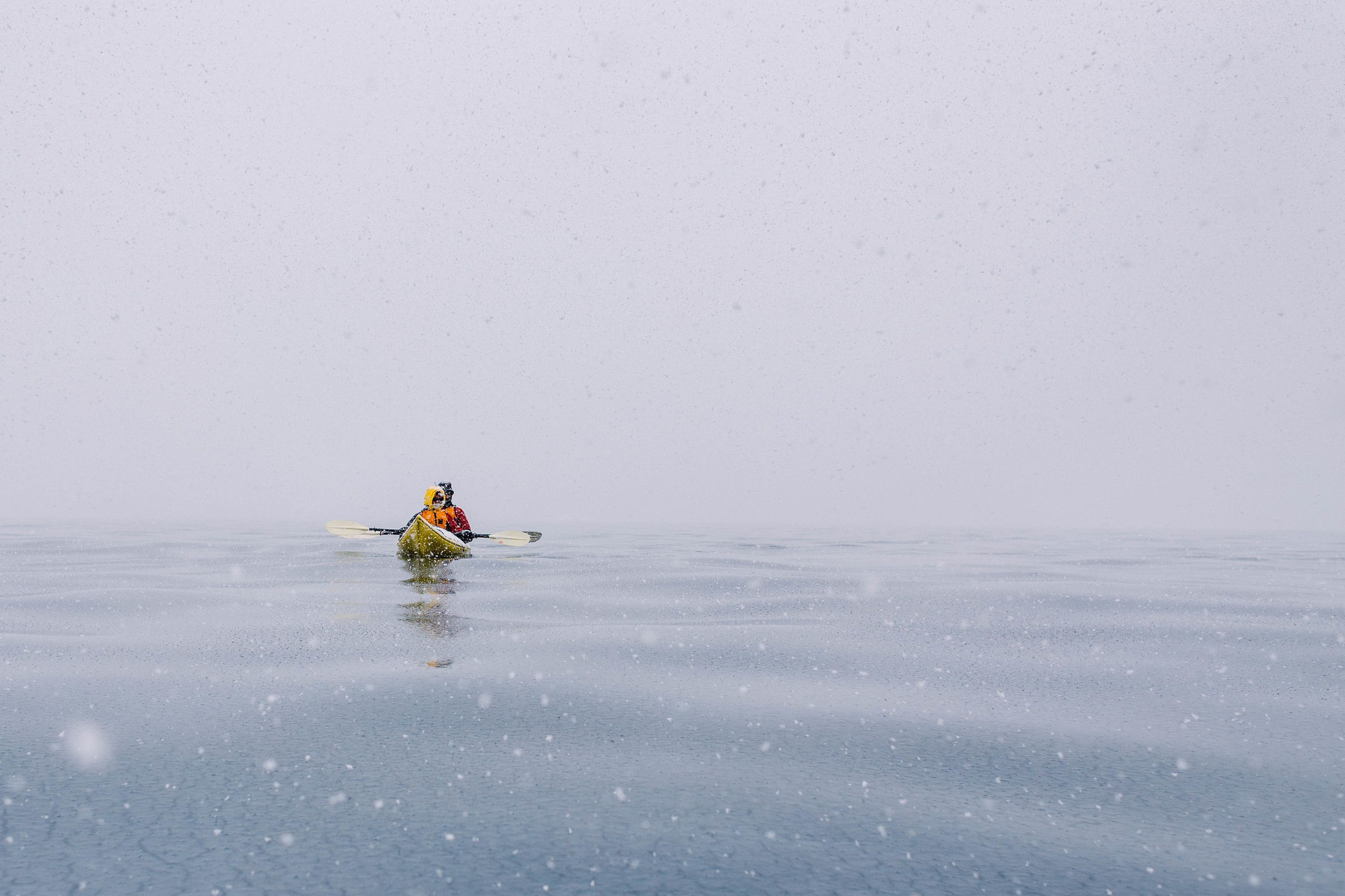 Marie and Nick peacefully await the rest of the kayakers as the snow falls beautifully around them. Salvesen Cove, Antarctica.